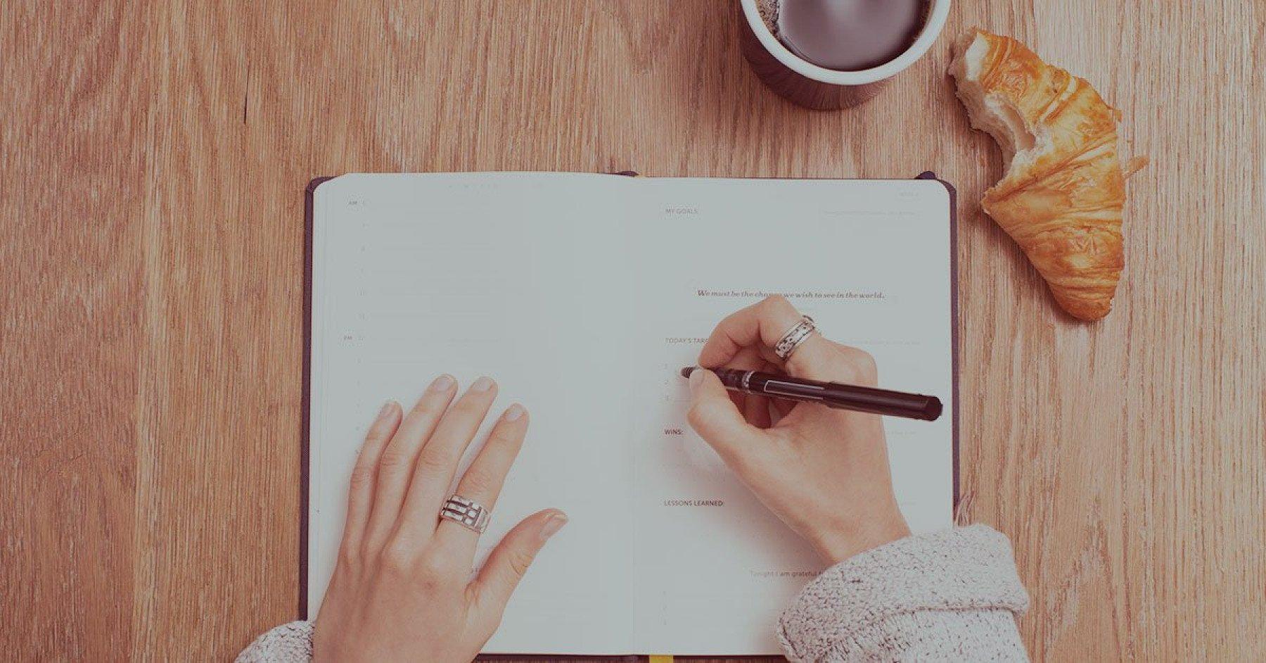 Person skriver i ett anteckningsblock med en croissant och kaffe bredvid