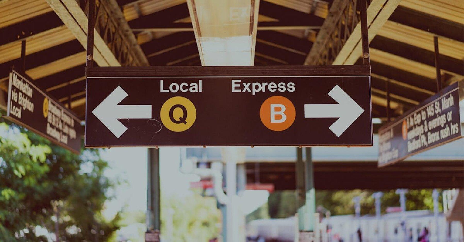 Bild på tågstation med skyltar där de står Local och Express