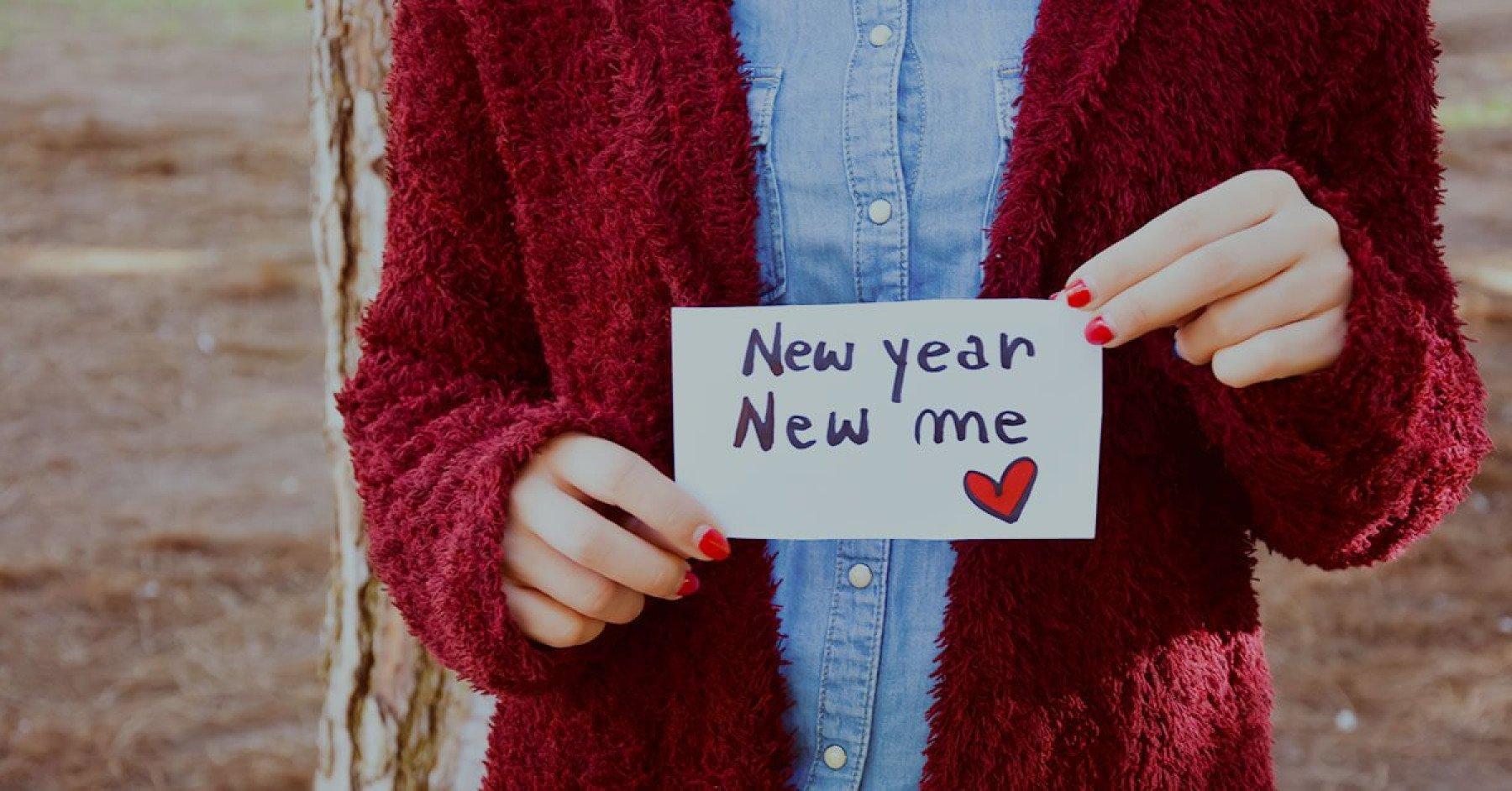 En person som håller upp en lapp med texten New year New me