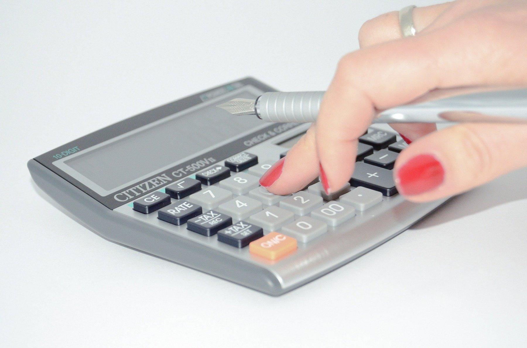 En hand som knappar på en miniräknare