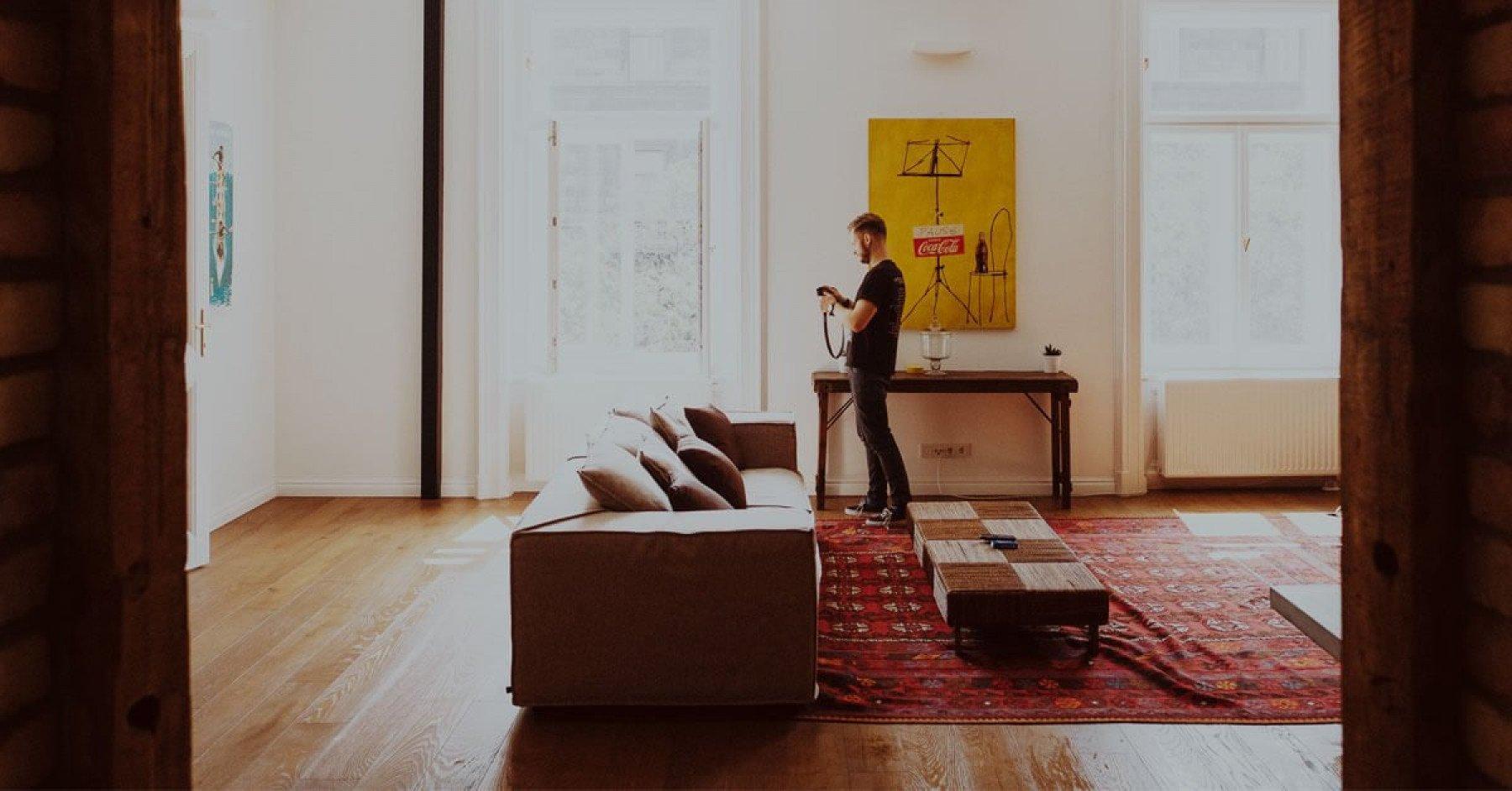 Man i vardagsrum som fotograferar tavlor