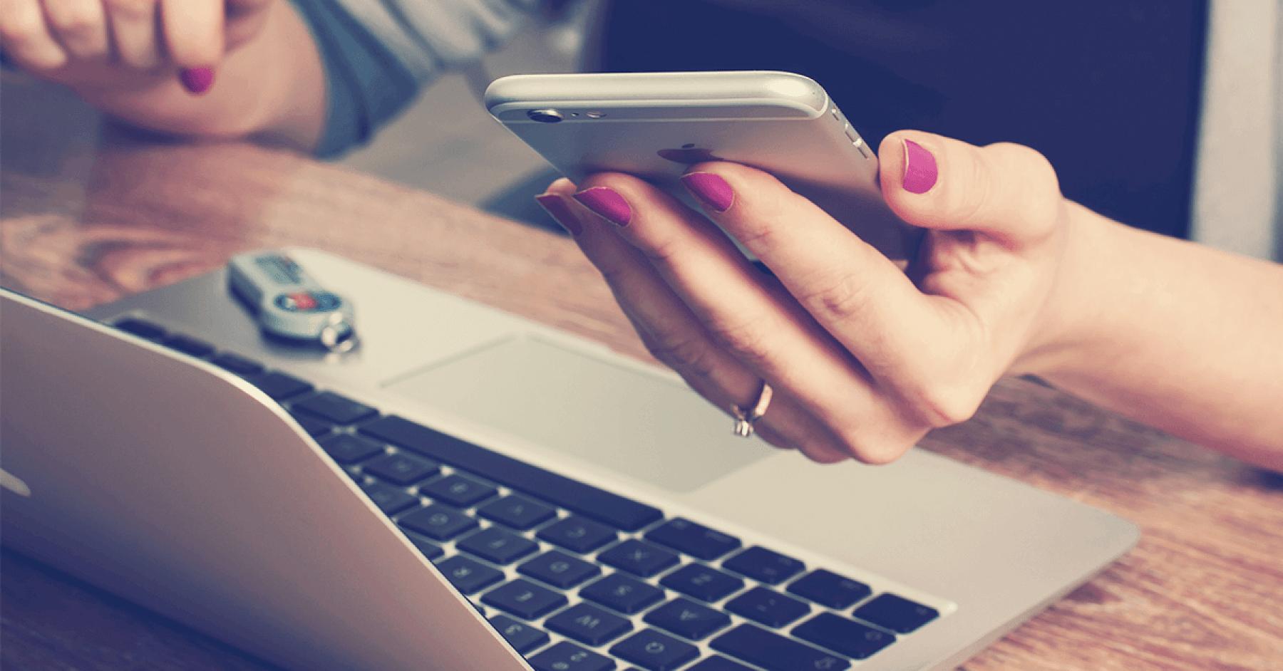 Kvinna som sitter vid ett bord med sin laptop och mobil