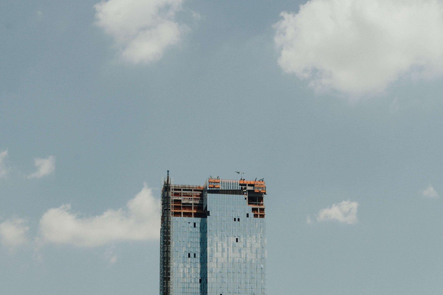En byggnation av en hög byggnad med glasfasad