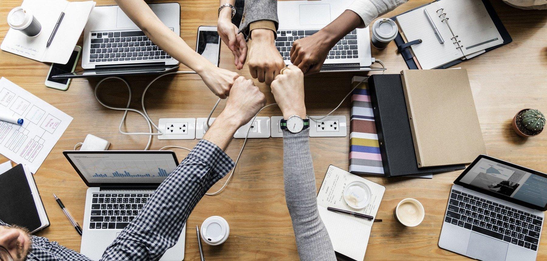 fem personer göra fist bump över ett bord med datorer