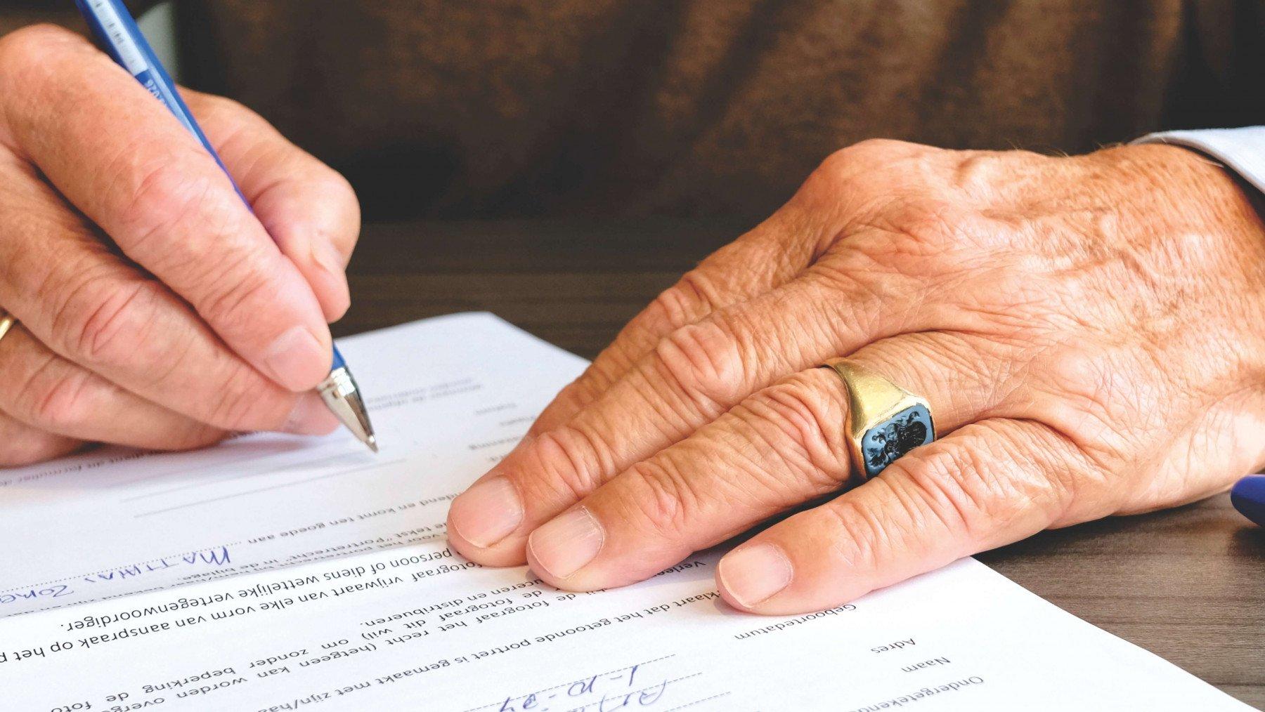 Manshänder som skriver på ett avtal
