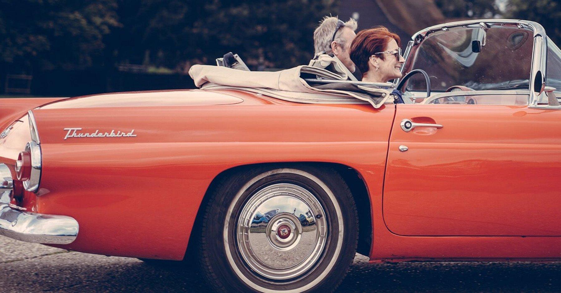 En man och en kvinna kör en klassisk veteranbil