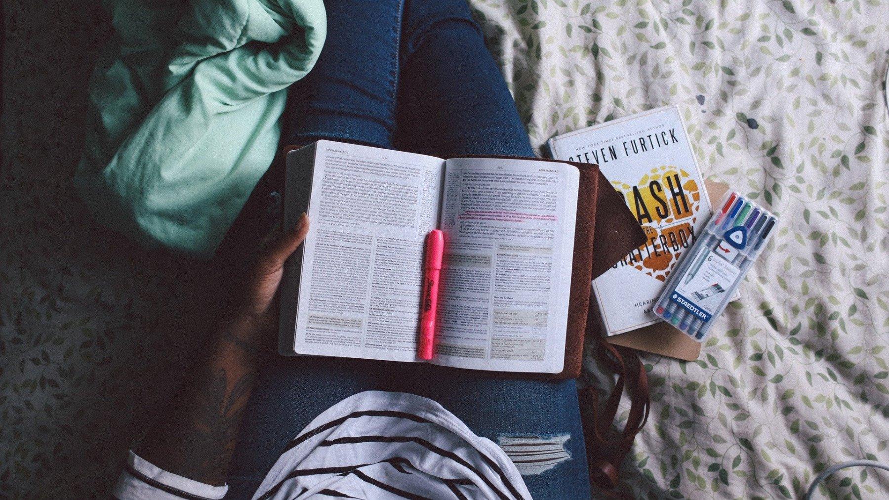 Person sitter i säng med böcker och överstrykningspennor