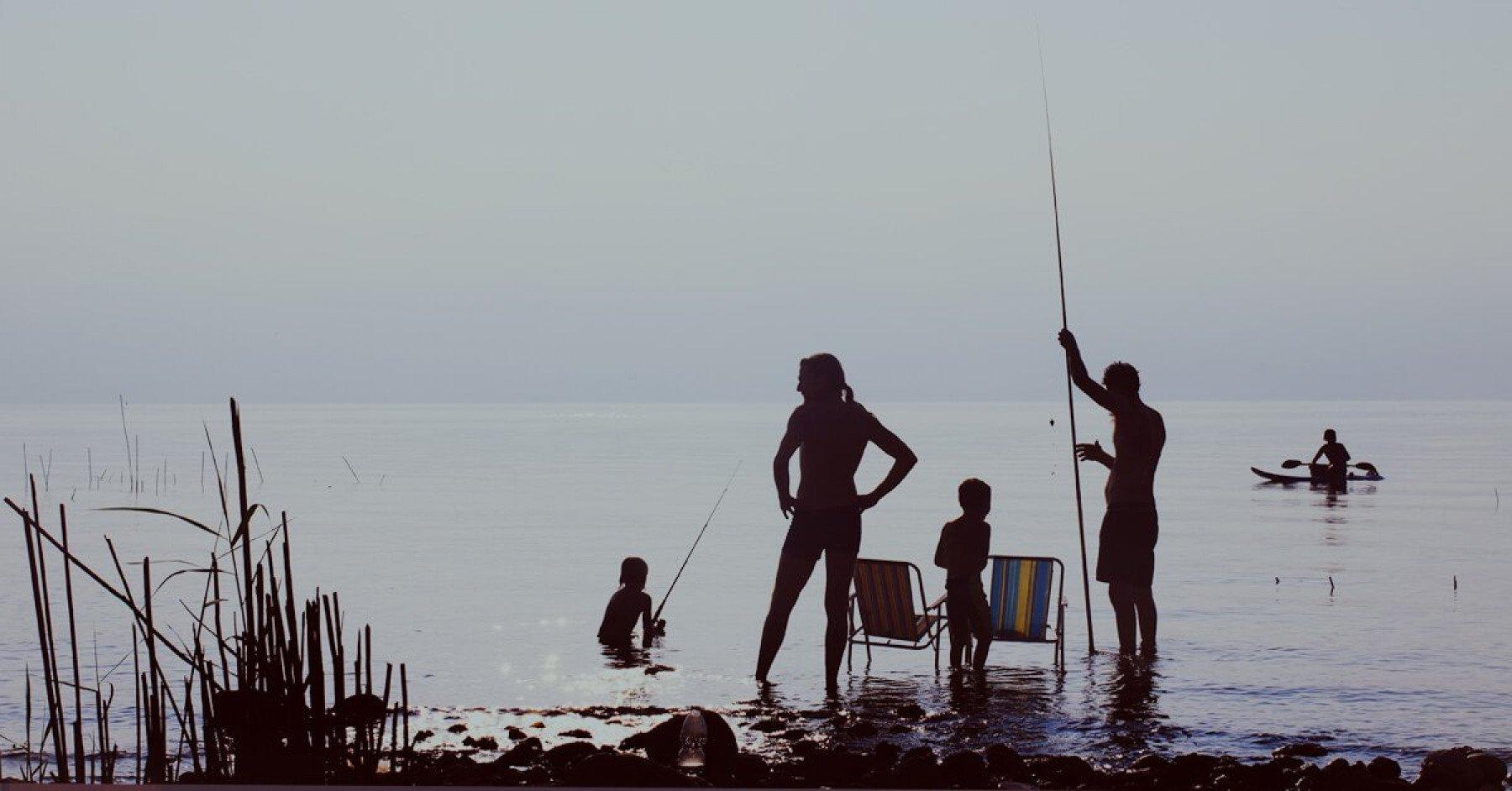 Familj som badar vid en sandstrand