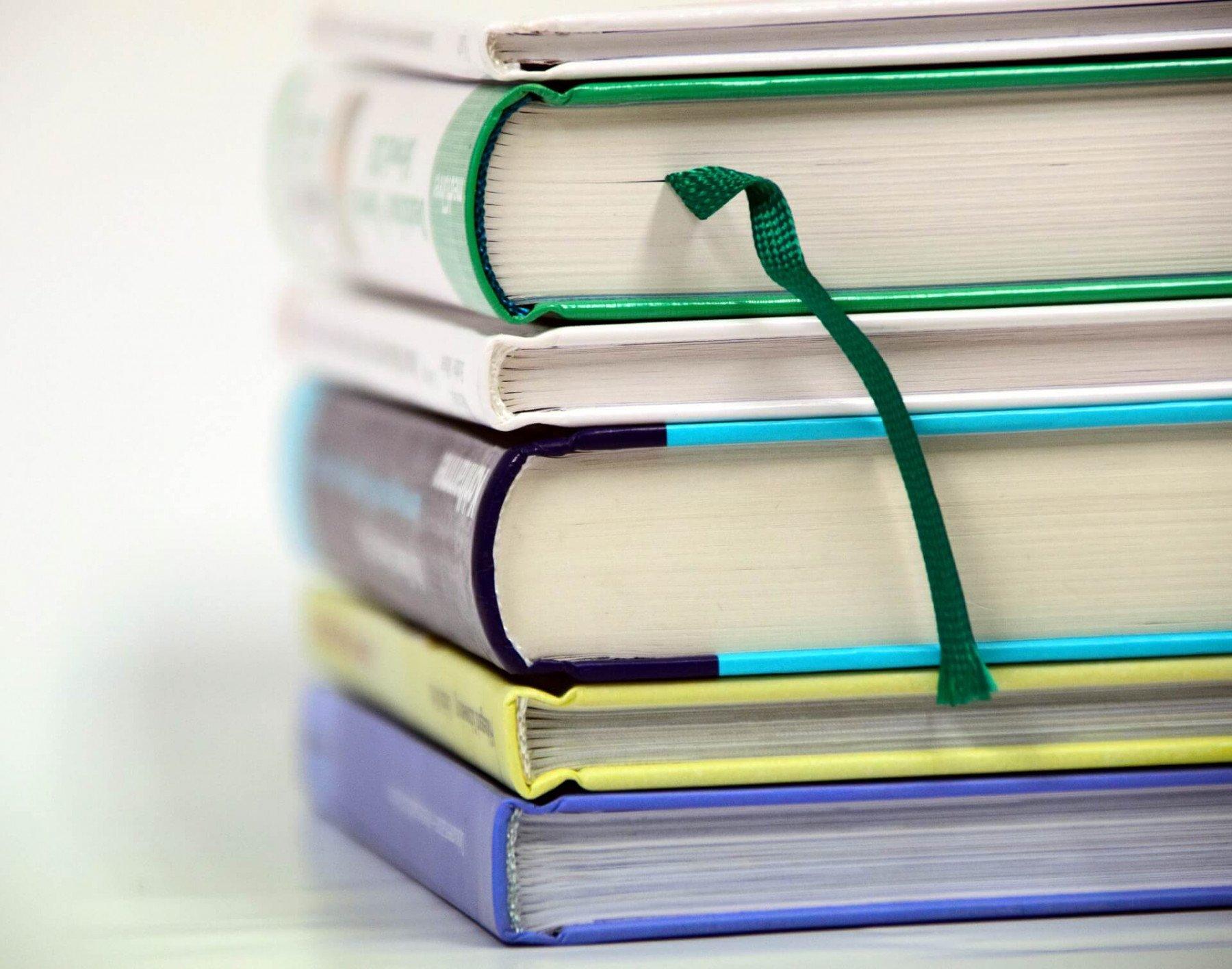 Sex stycken böcker ligger på varandra på ett bord