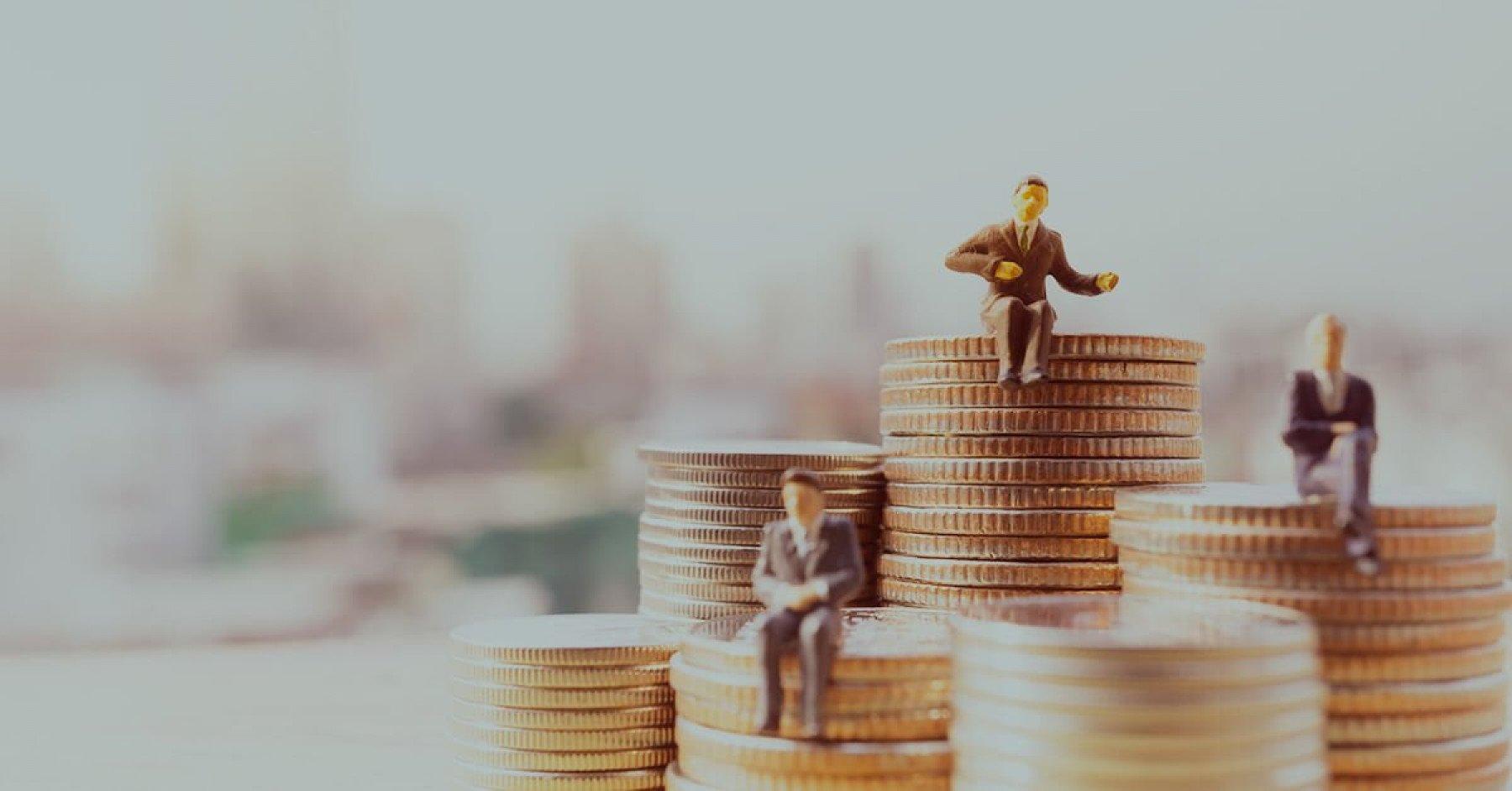 Mynt staplade på varandra i olika stora högar. Miniatyr figurer sitter ovanpå
