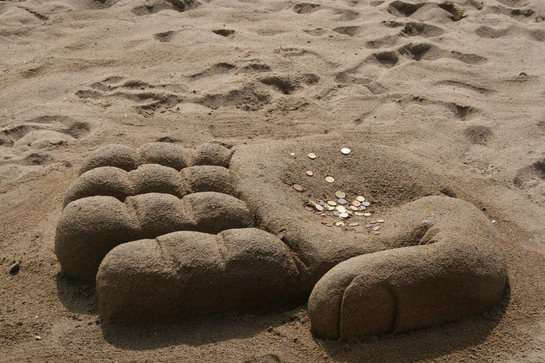 En strand med ett sandslott som liknar en hand. På handen ligger det mynt