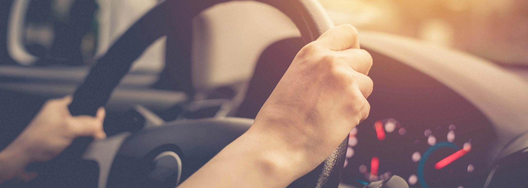 Två händer som håller i en bilratt
