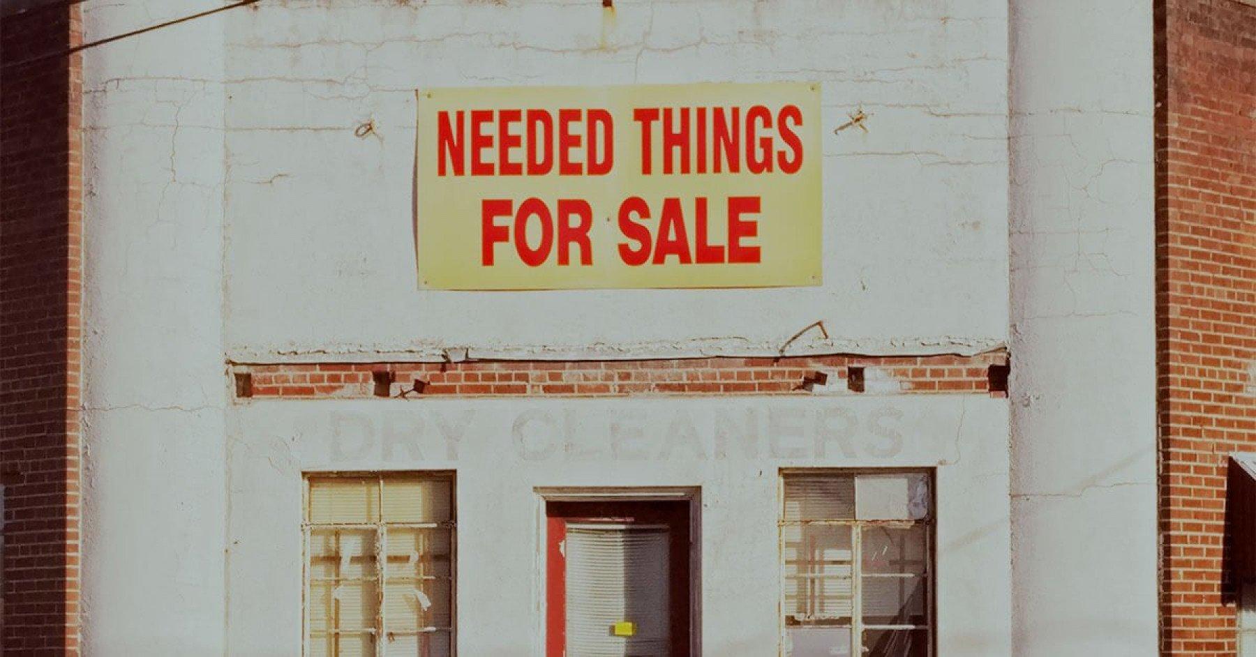 Bild på en tegelfast med en skylt där det står Needed things for sale