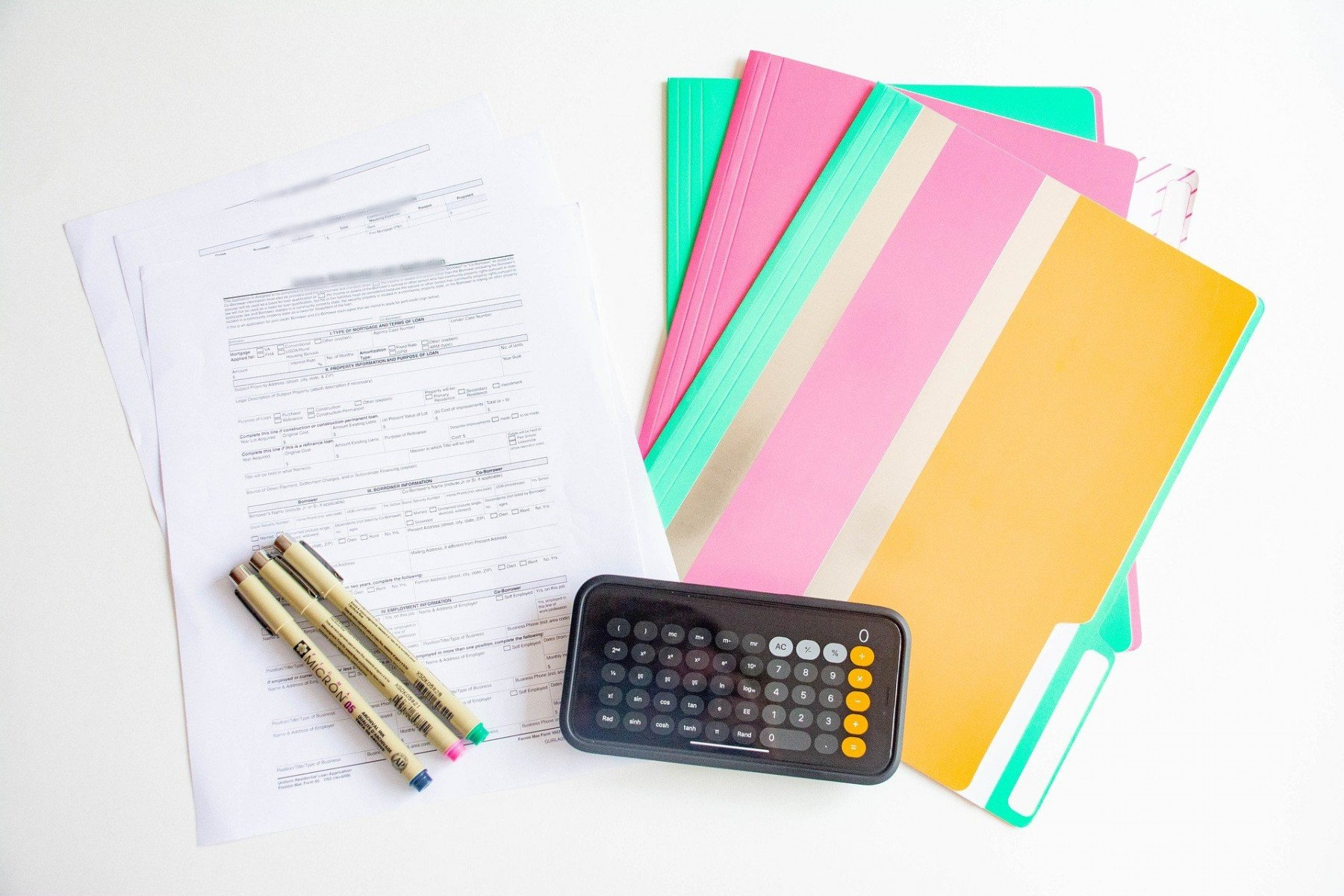 Avtal, pärmar och pennor ligger på ett bord med en mobil