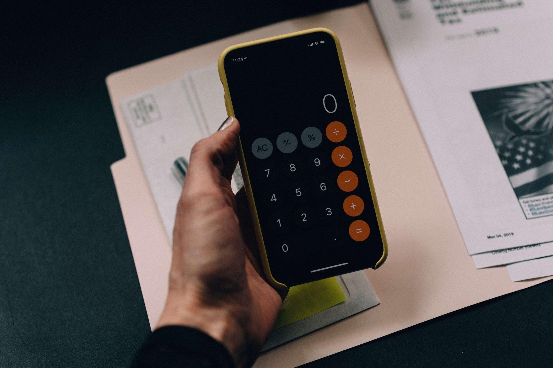 Person håller i mobil med miniräknaren framme