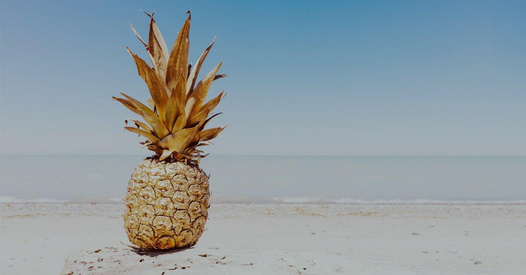 En guldig ananas på en solig sandstrand med vågor i bakgrunden