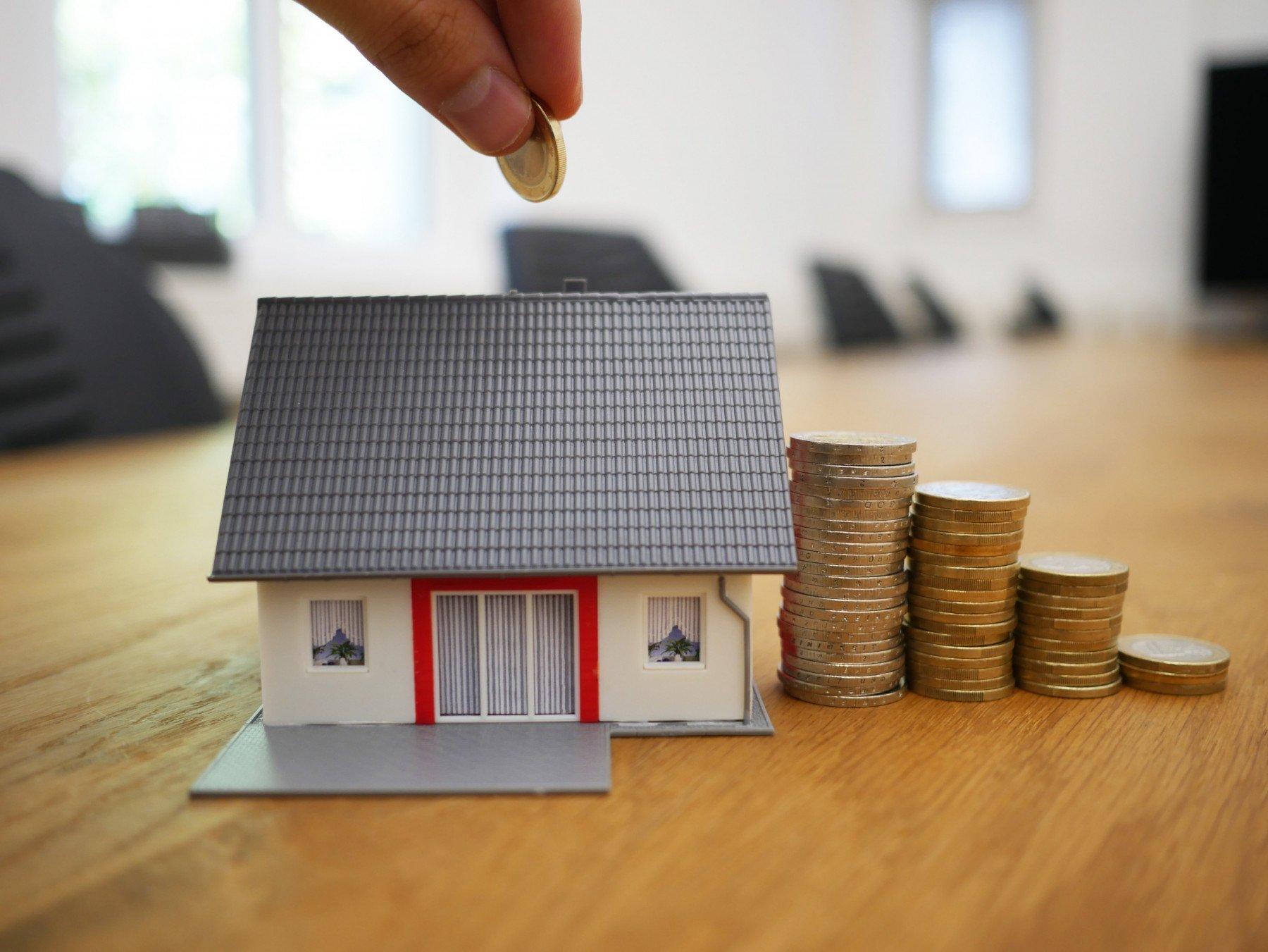Litet modellhus och 4 högar med mynt på ett bord