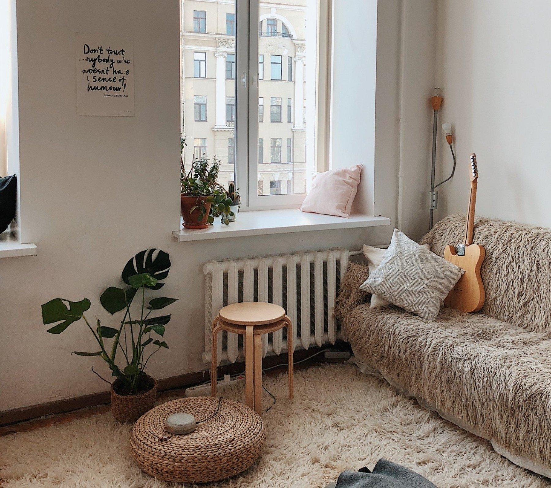 Bild inuti en lägenhet med soffa, gitarr och pallar