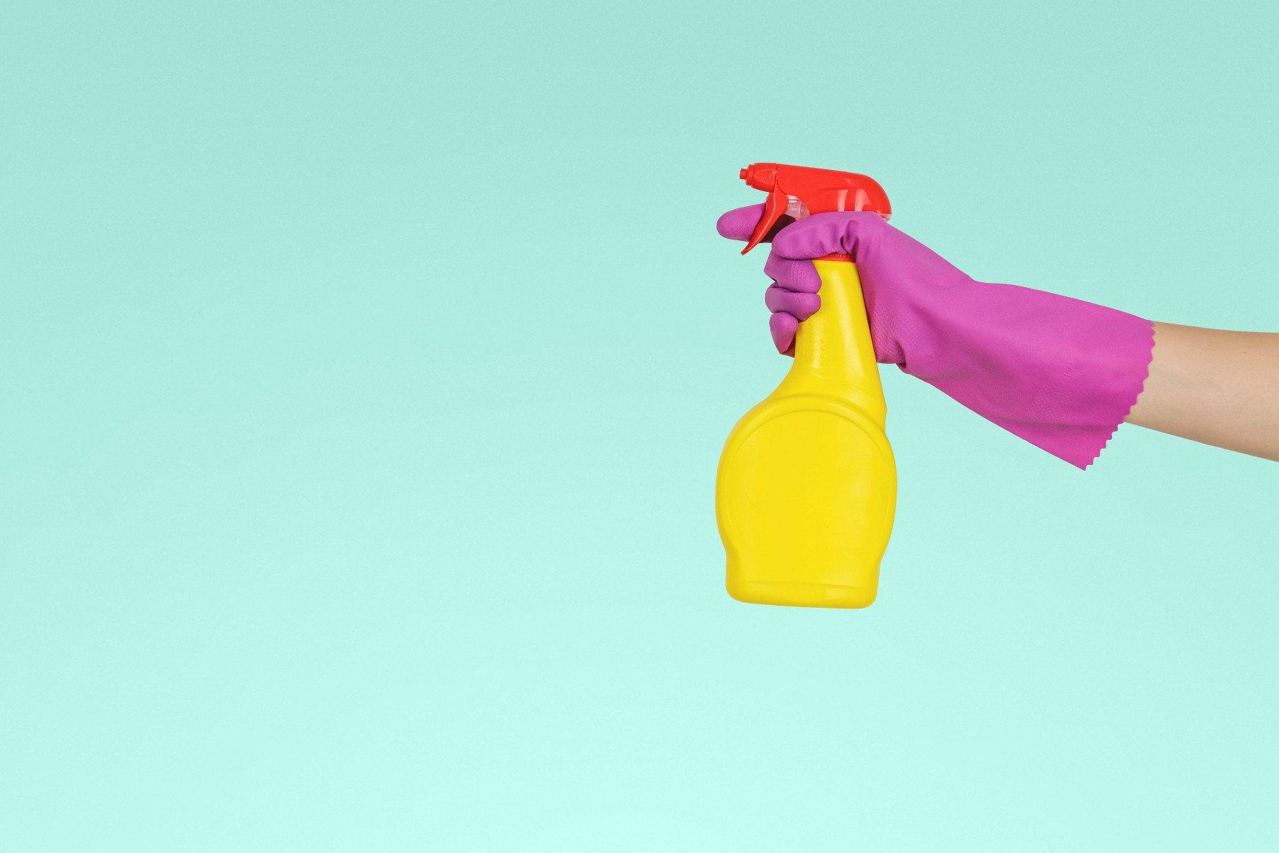 Hand med gummihanske som håller i en sprayflaska