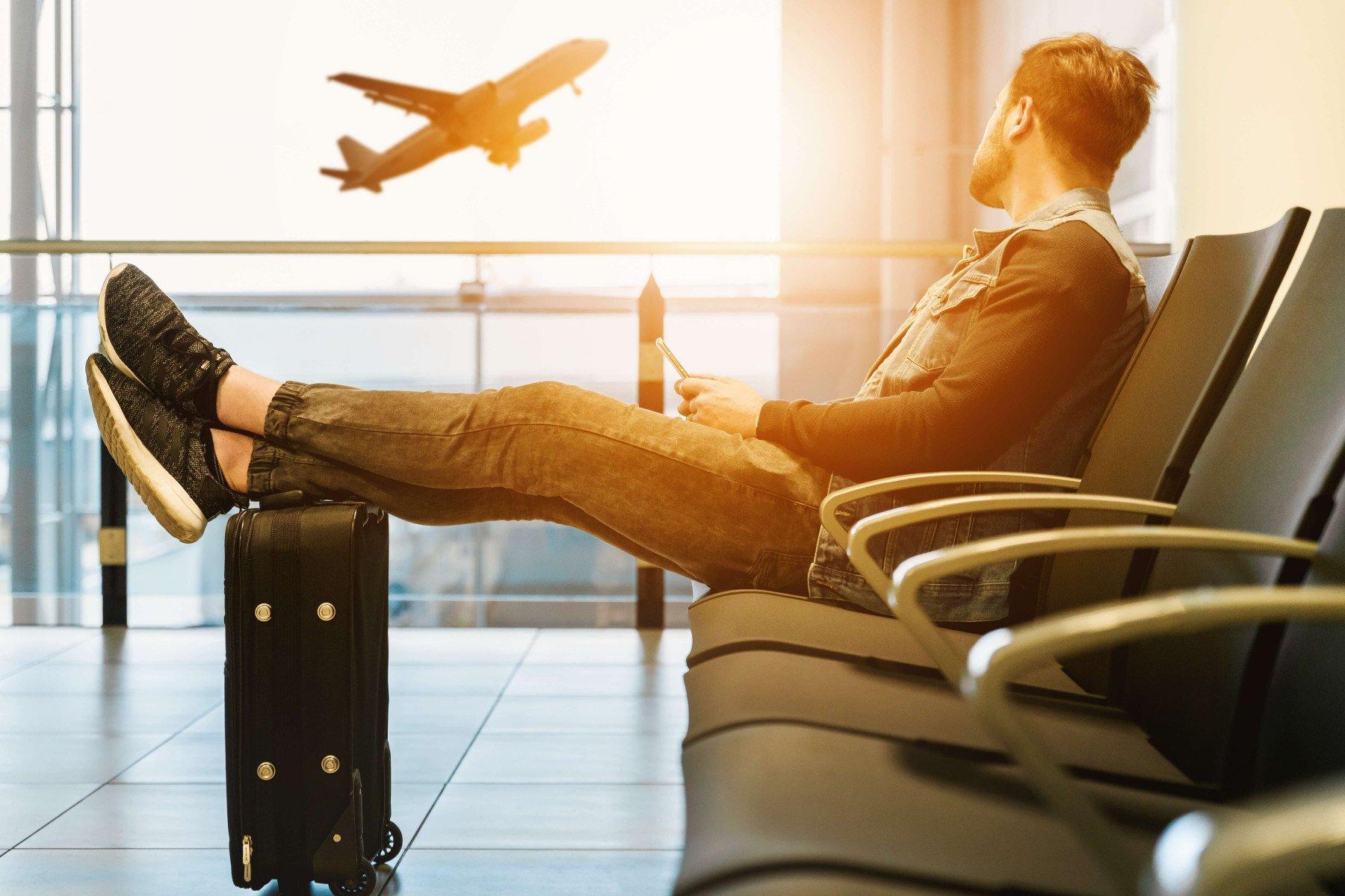 En man som sitter på en flygplats och ser ett plan som lyfter
