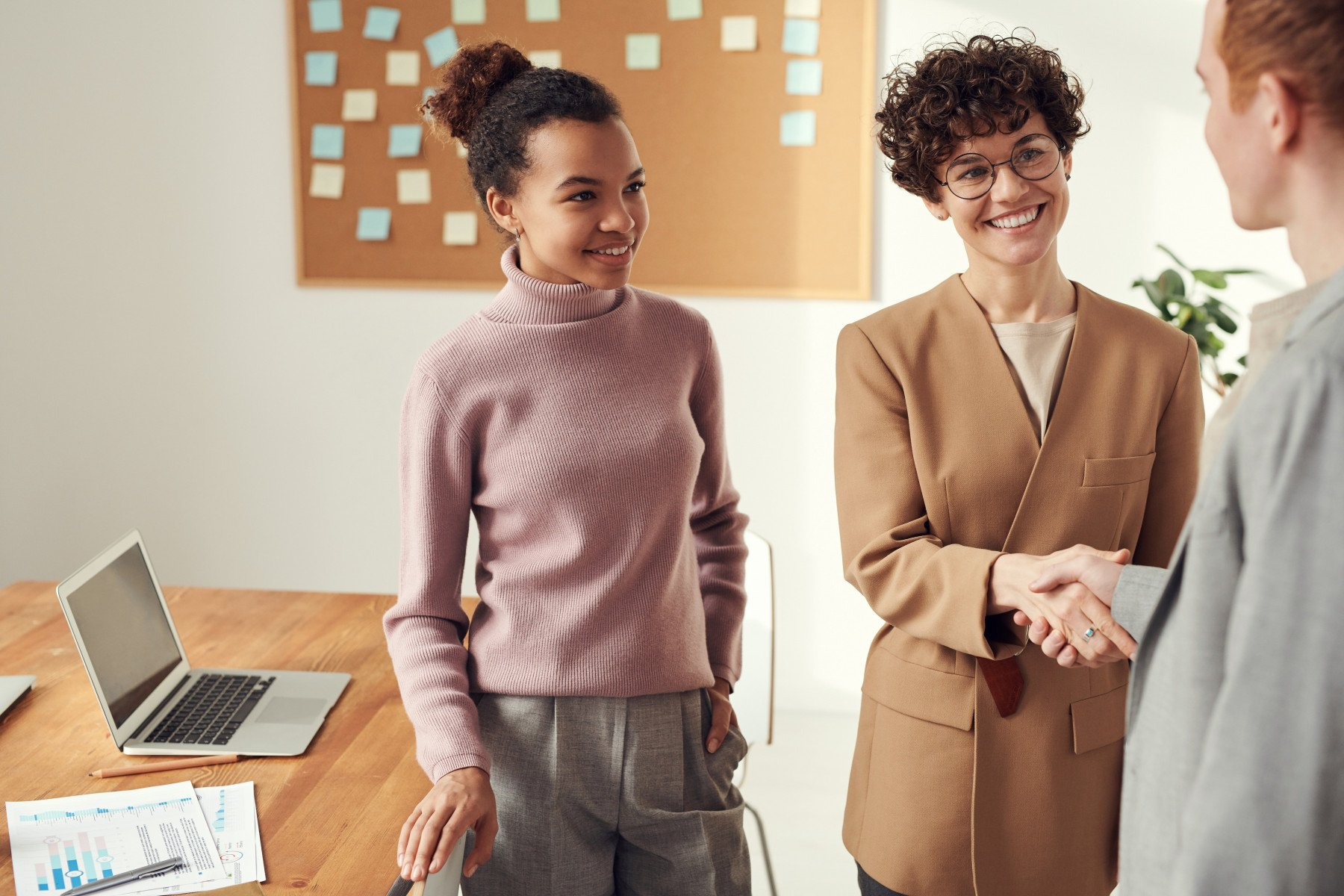 Tre unga personer som skakar hand med varandra i en kontorsmiljö