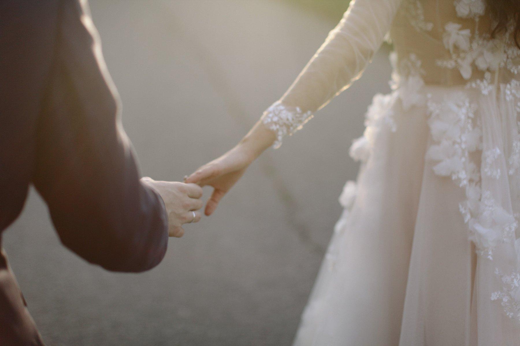 Bröllopspar håller varandra i handen utomhus
