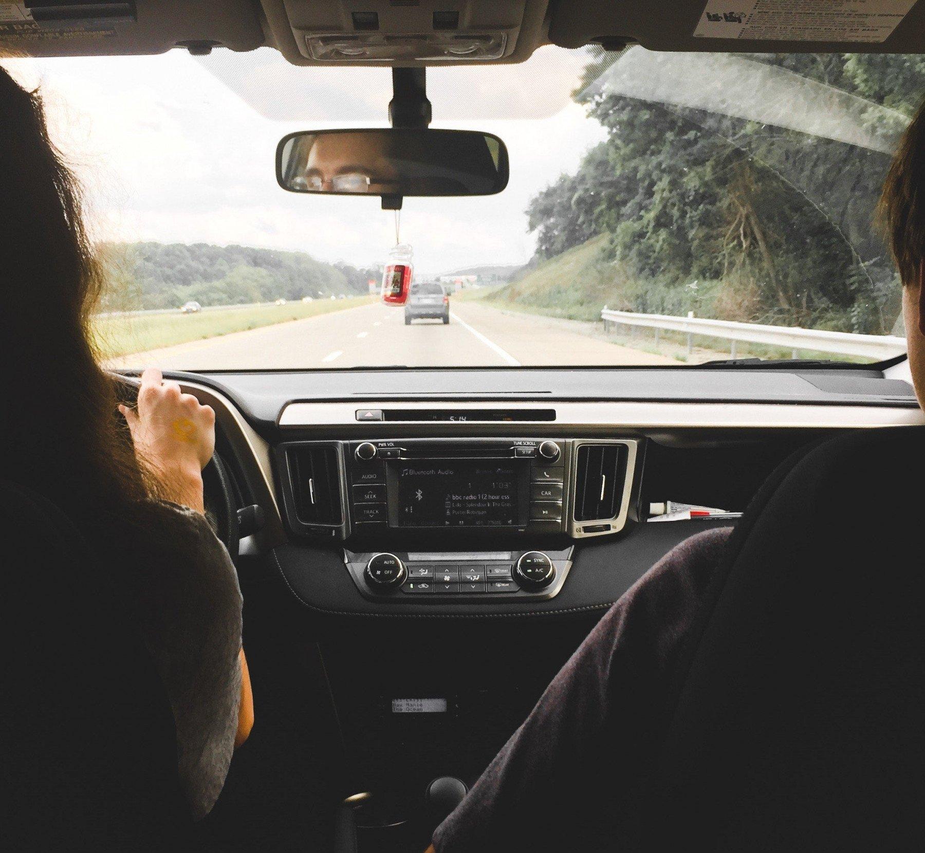 Personer sitter inuti en bil som kör på en landsväg