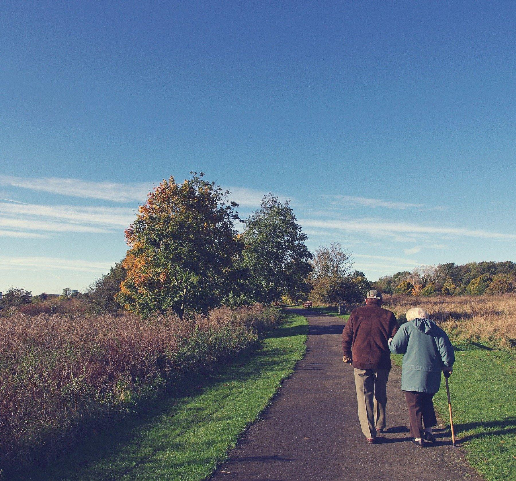 Två äldre personer går på en grusväg i naturen