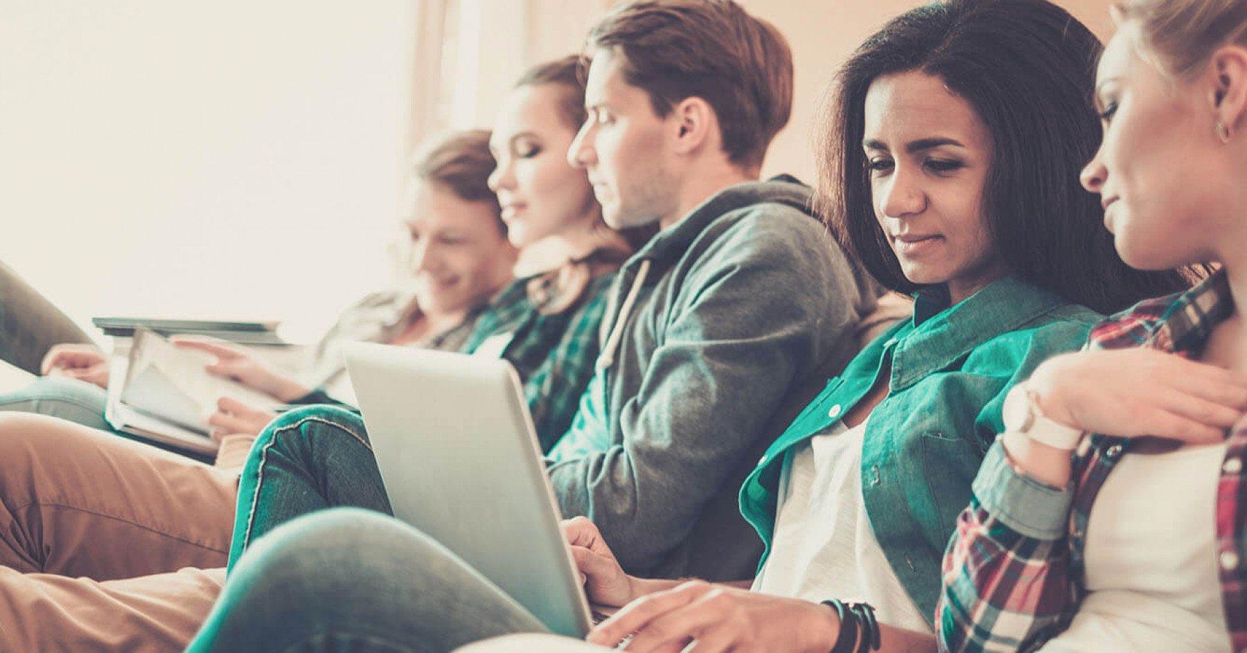 Människor sitter i en soffa med bärbara datorer