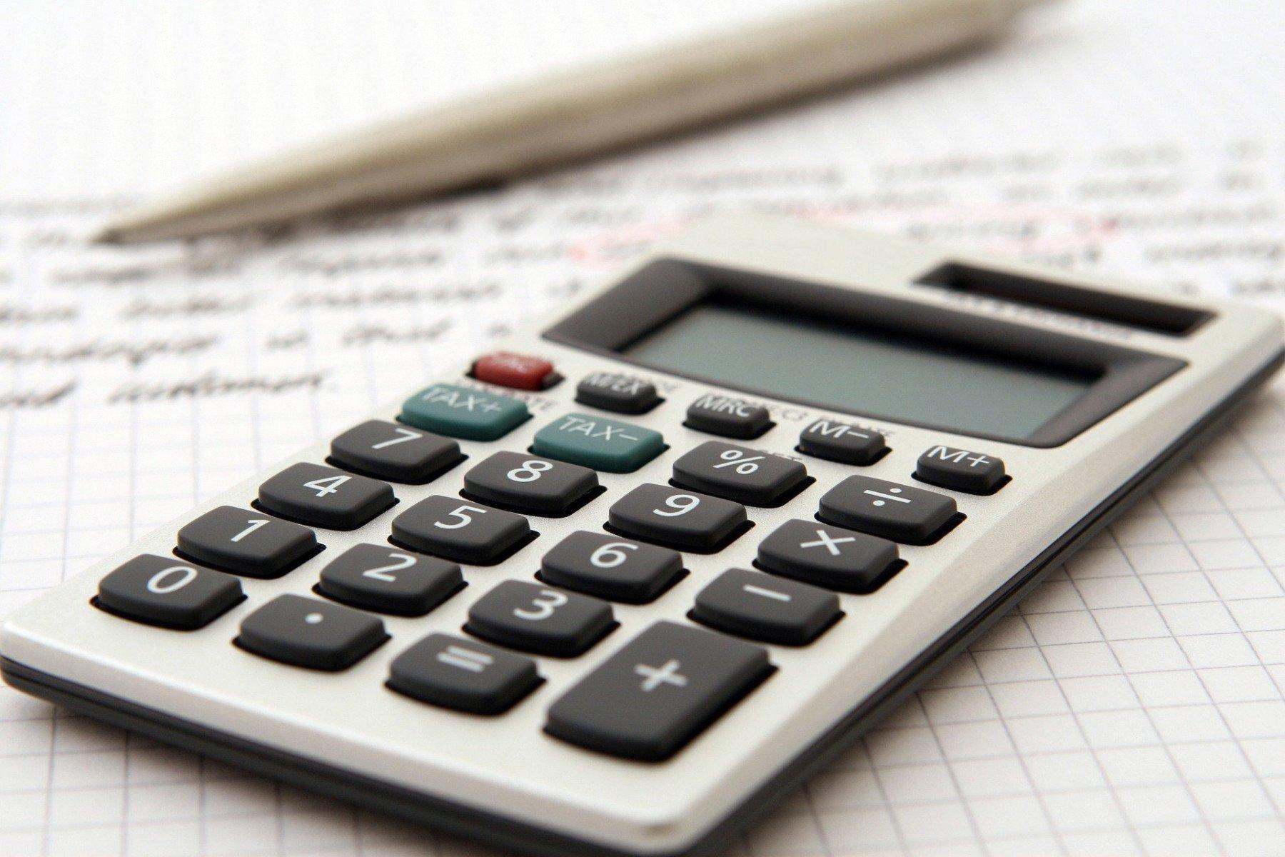 En miniräknare bredvid ett papper och penna
