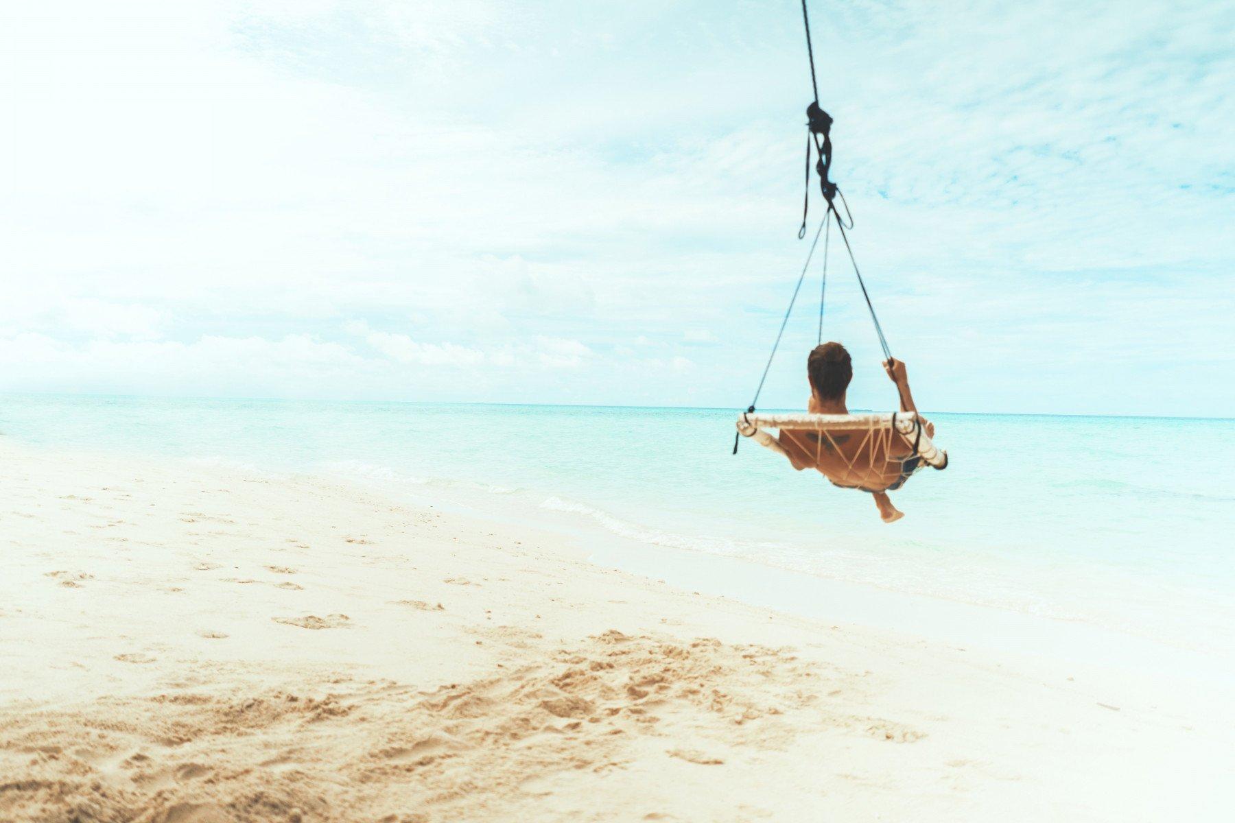 En person sitter på i en gunga vid en tropisk strand