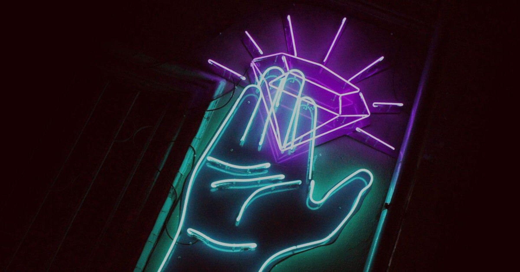 En neonskylt föreställer en hand som håller i en diamant