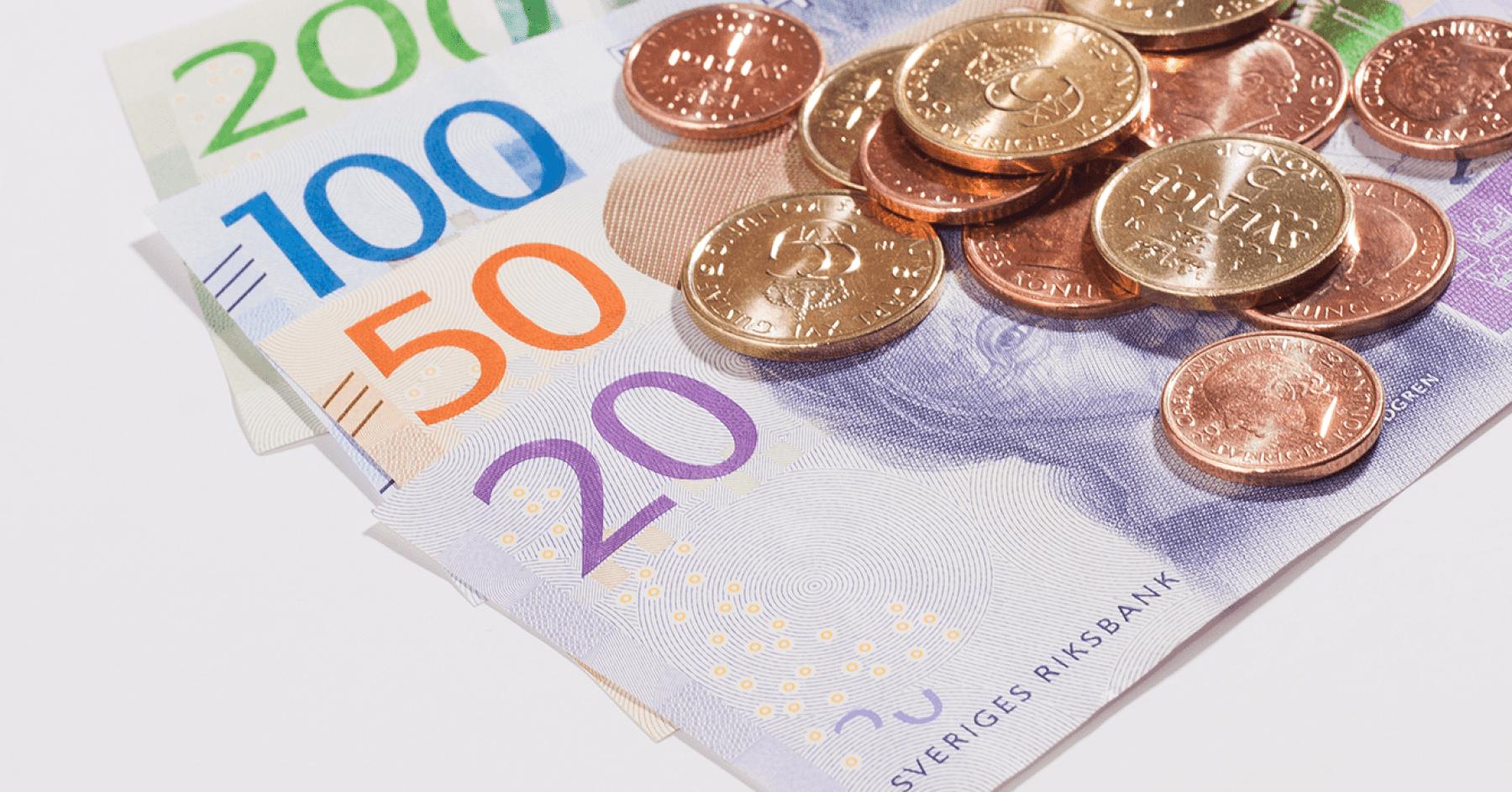 Svenska sedlar och mynt ligger på ett bord