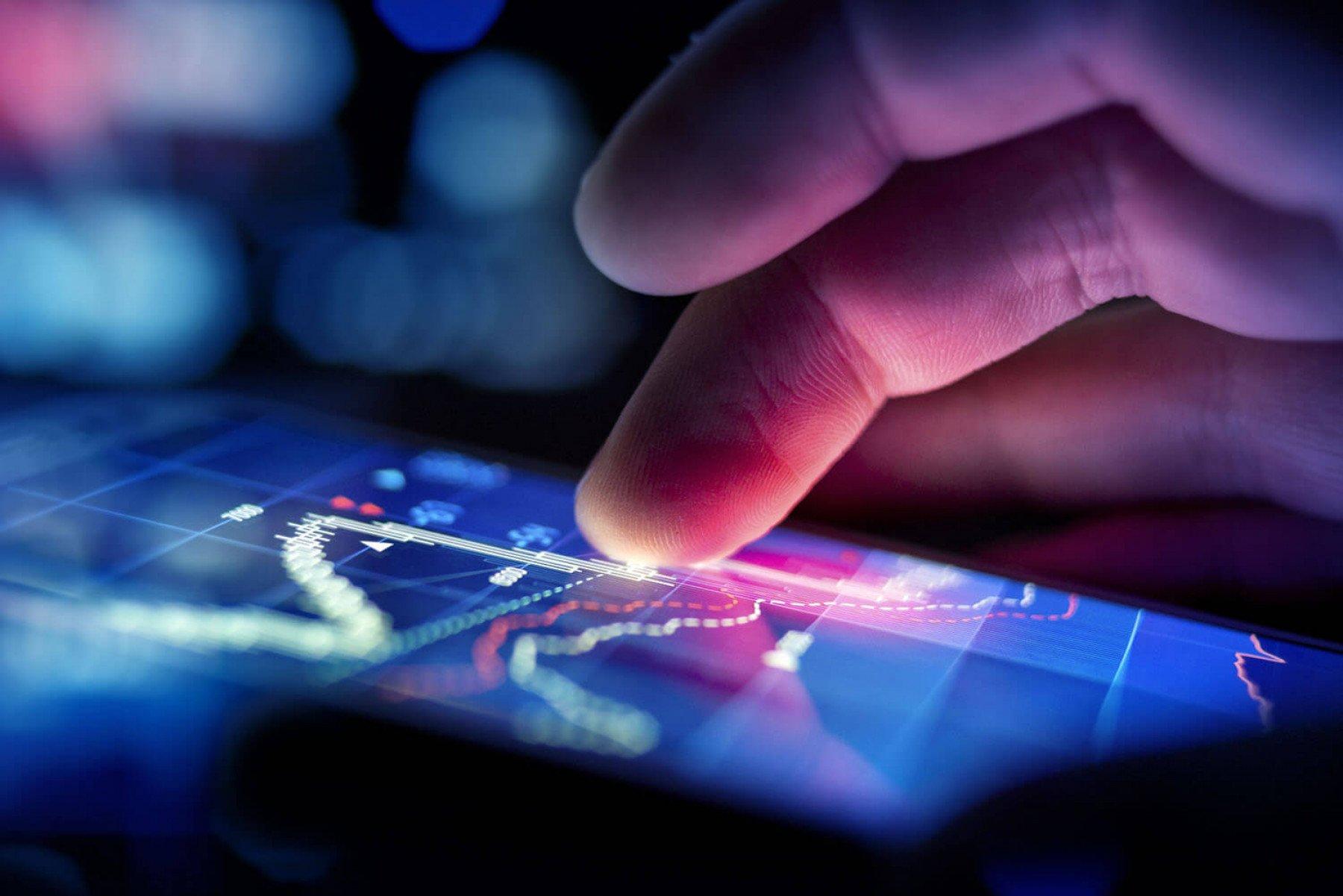Person som pekar på en skärm som visar börskurs