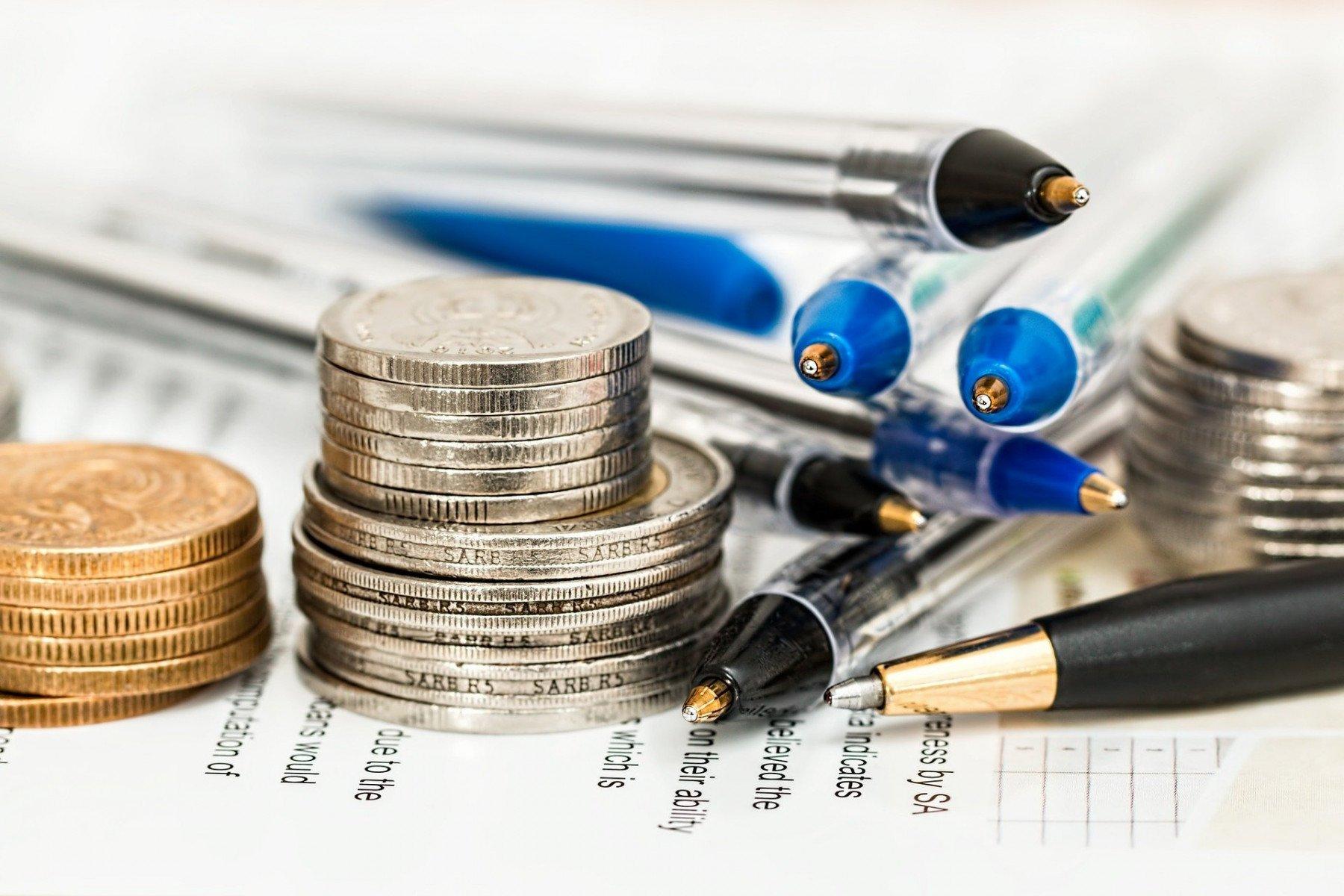 Mynt och pennor i en hög