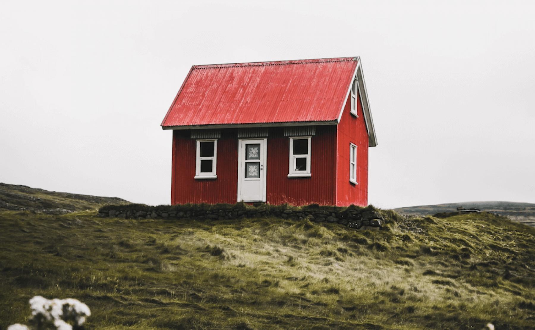 Rött hus med vita knutar i öde landskap