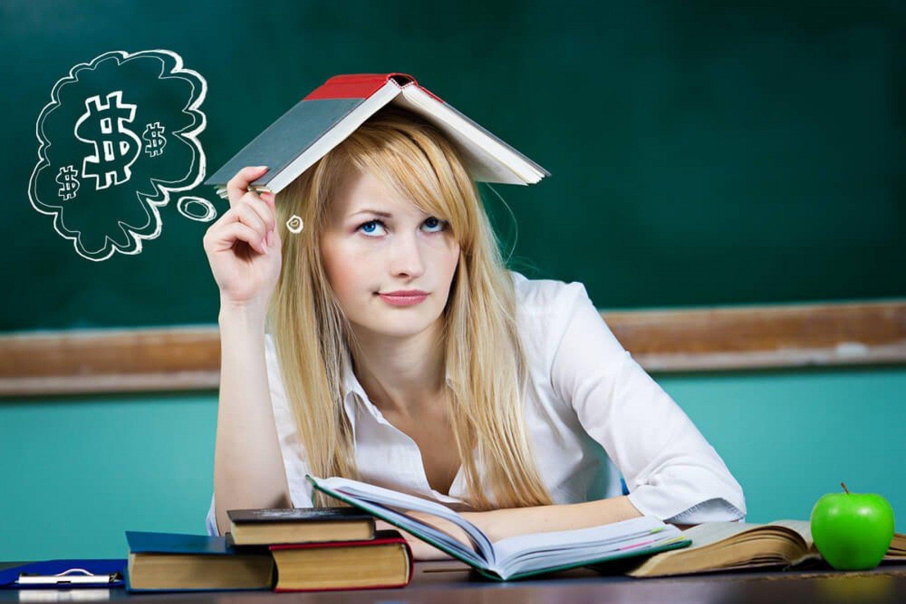 Tjej som sitter i ett klassrum med en bok över huvudet och tänker på pengar