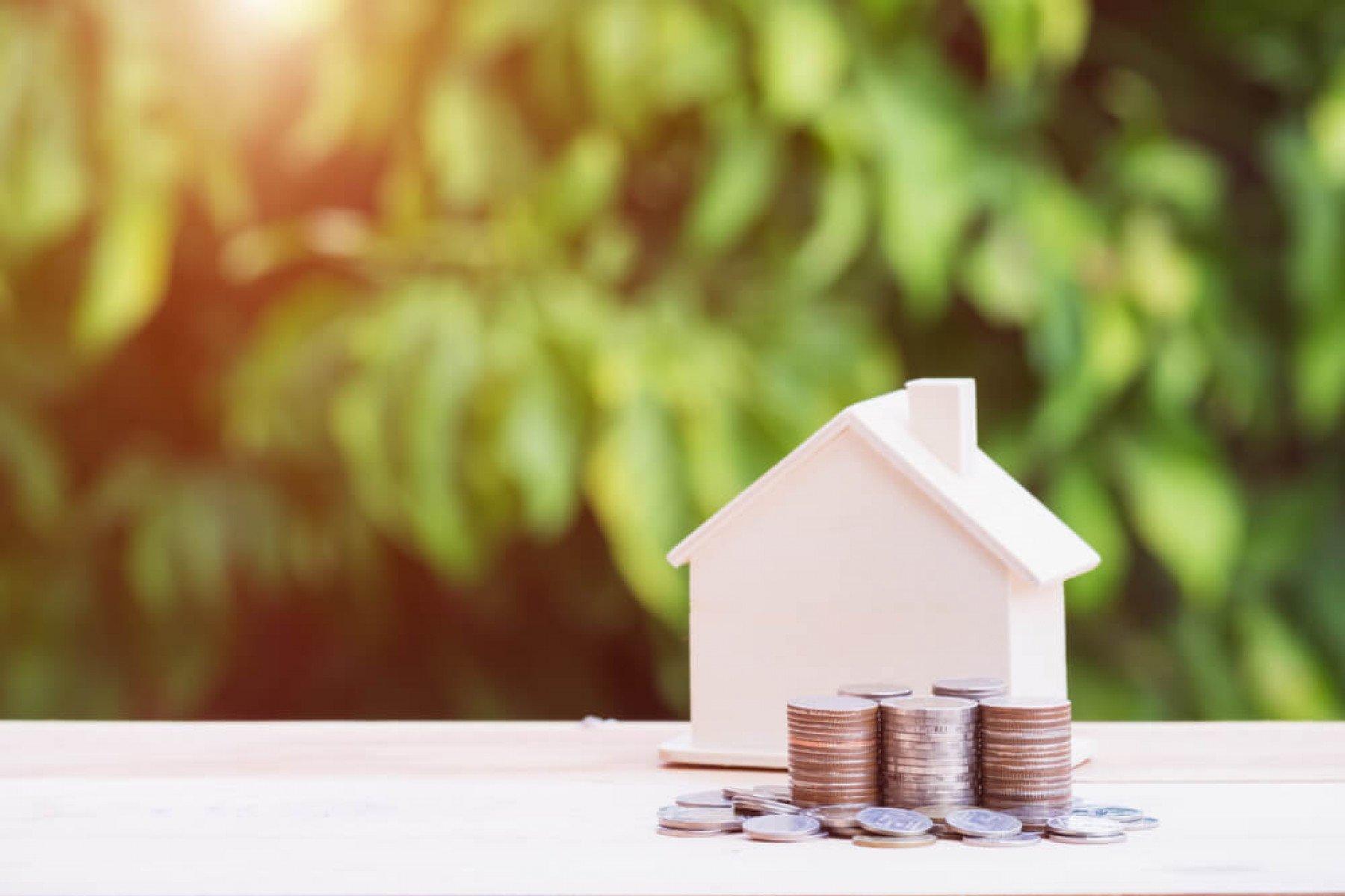 Miniatyrhus i trä med mynt i staplar framför