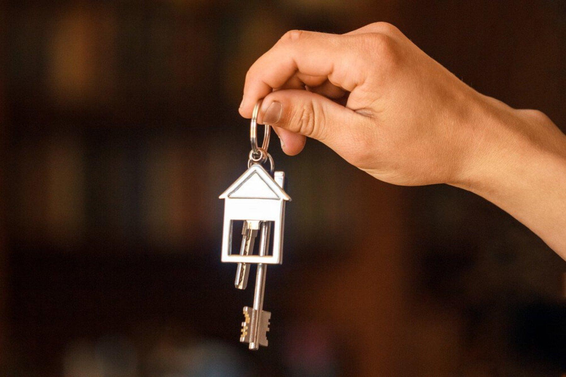 Person som håller upp nycklar med ett hus på