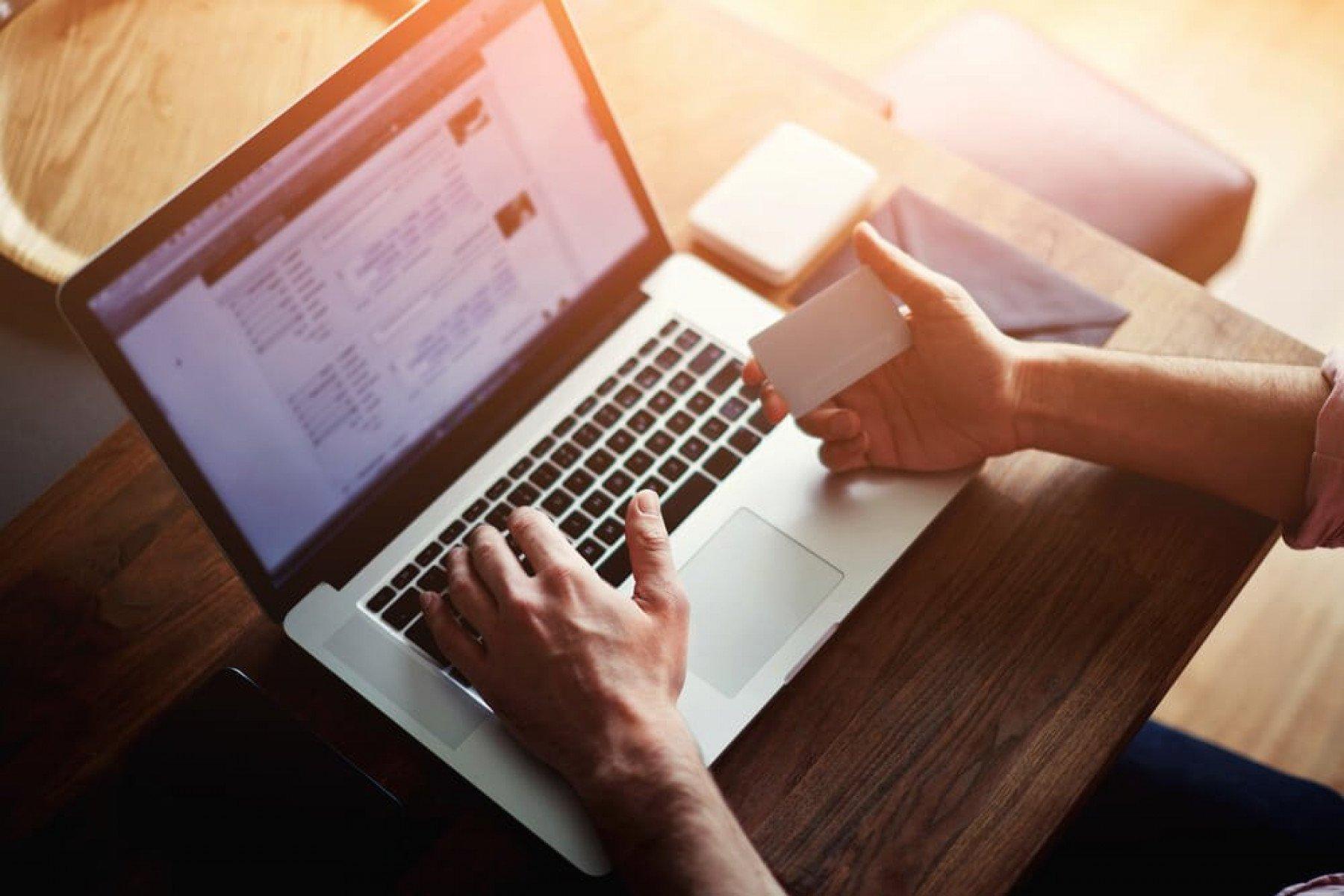 En person registrerar sitt kreditkort för ett köp på internet via sin laptop
