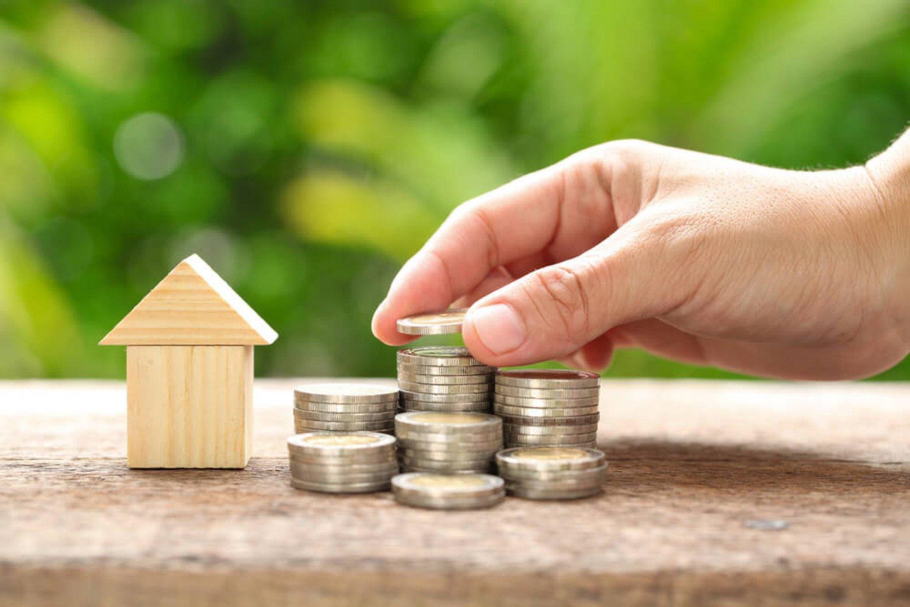 Ett Litet trähus och en hand som staplar mynt i 7 högar på ett bord