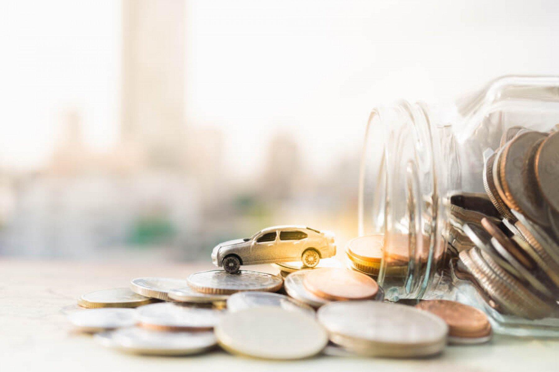 En glasburk ligger på ett bord med mynt ligger uthällda på ett bord. Ut ur glasburken kommer en leksaksbil