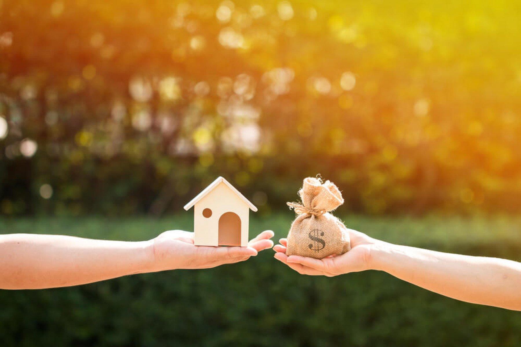 En hand som håller i ett litet trä hus och en hand som håller i en liten jutevävspåse med ett dollar tecken på