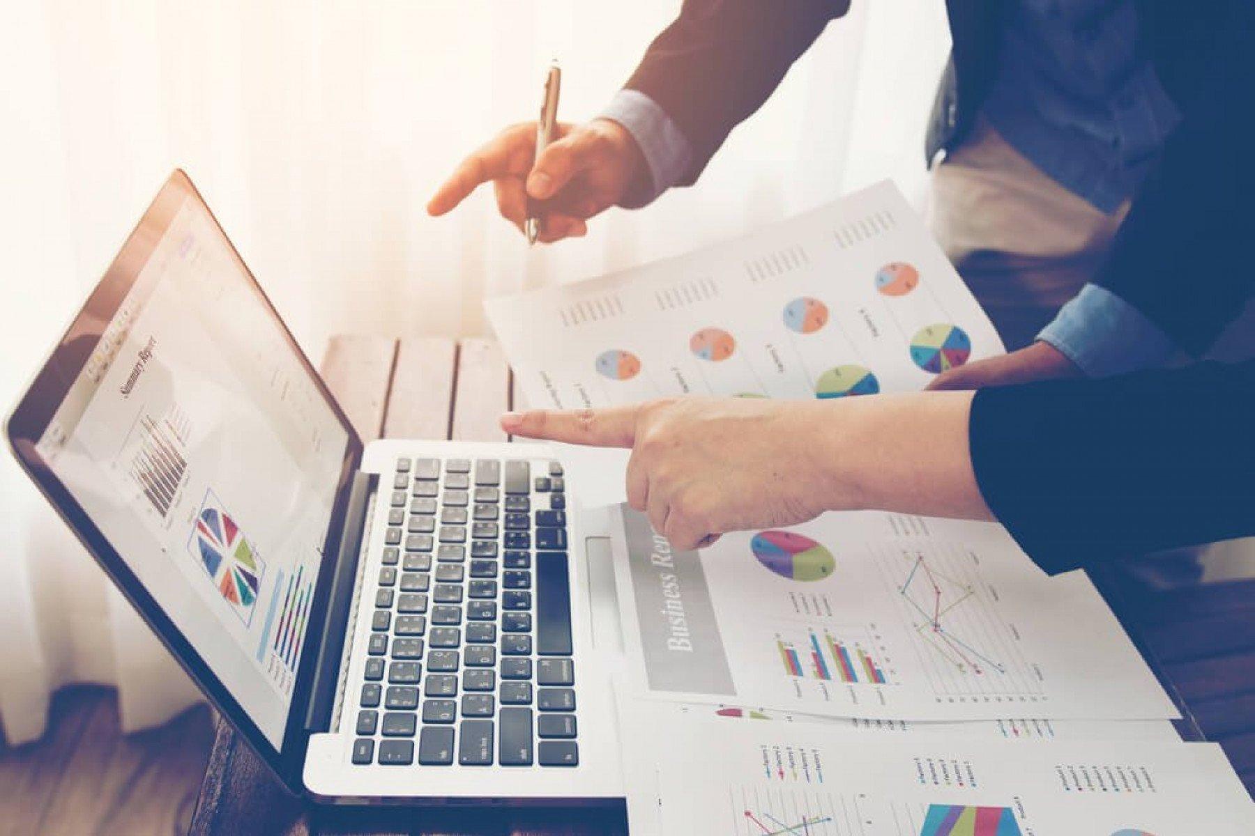 Två personer som pekar på en datorskärm med diagram och håller i dokument med diagram