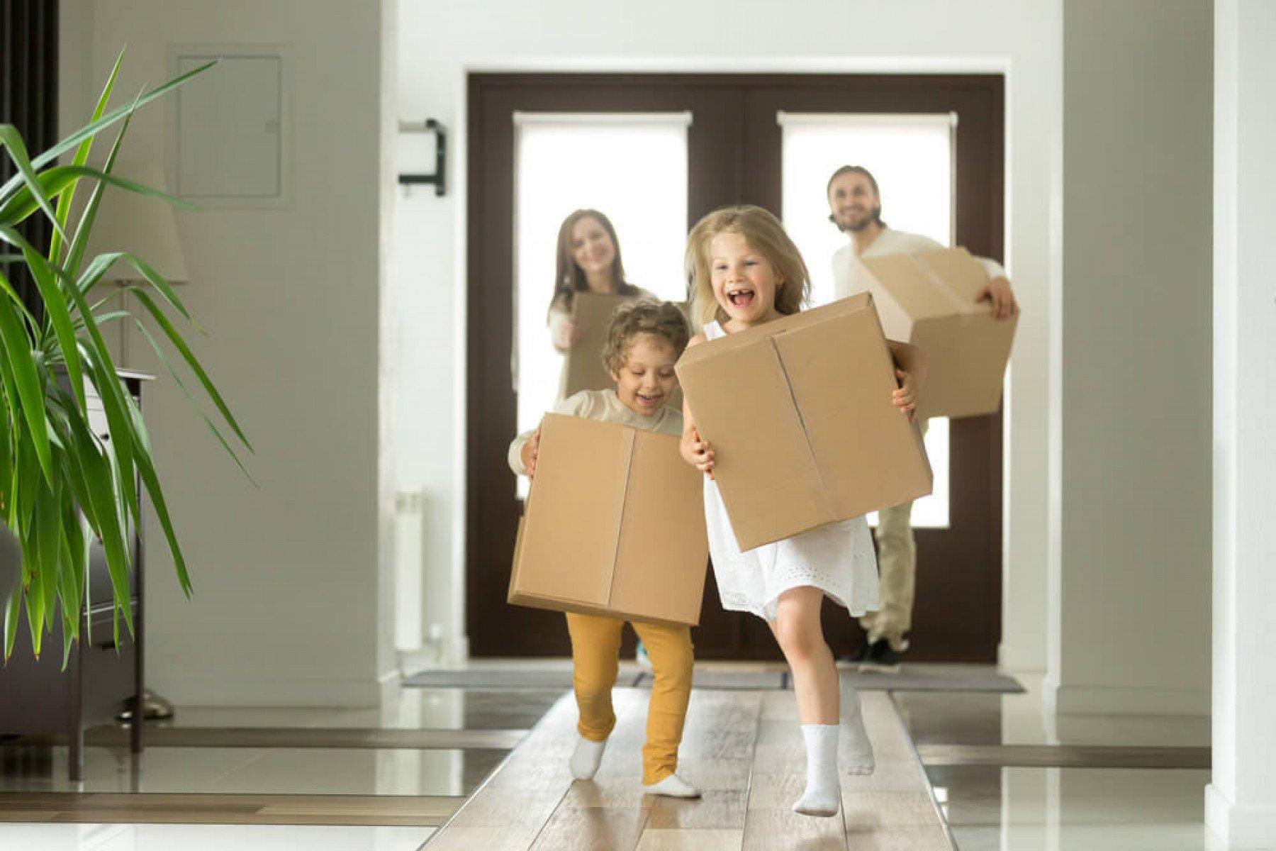 Familj springer in med flyttlådor i ett hus