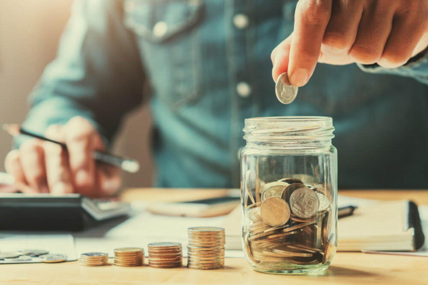 En person sitter med debit och kredit. Personen sätter mynt i en glasburk