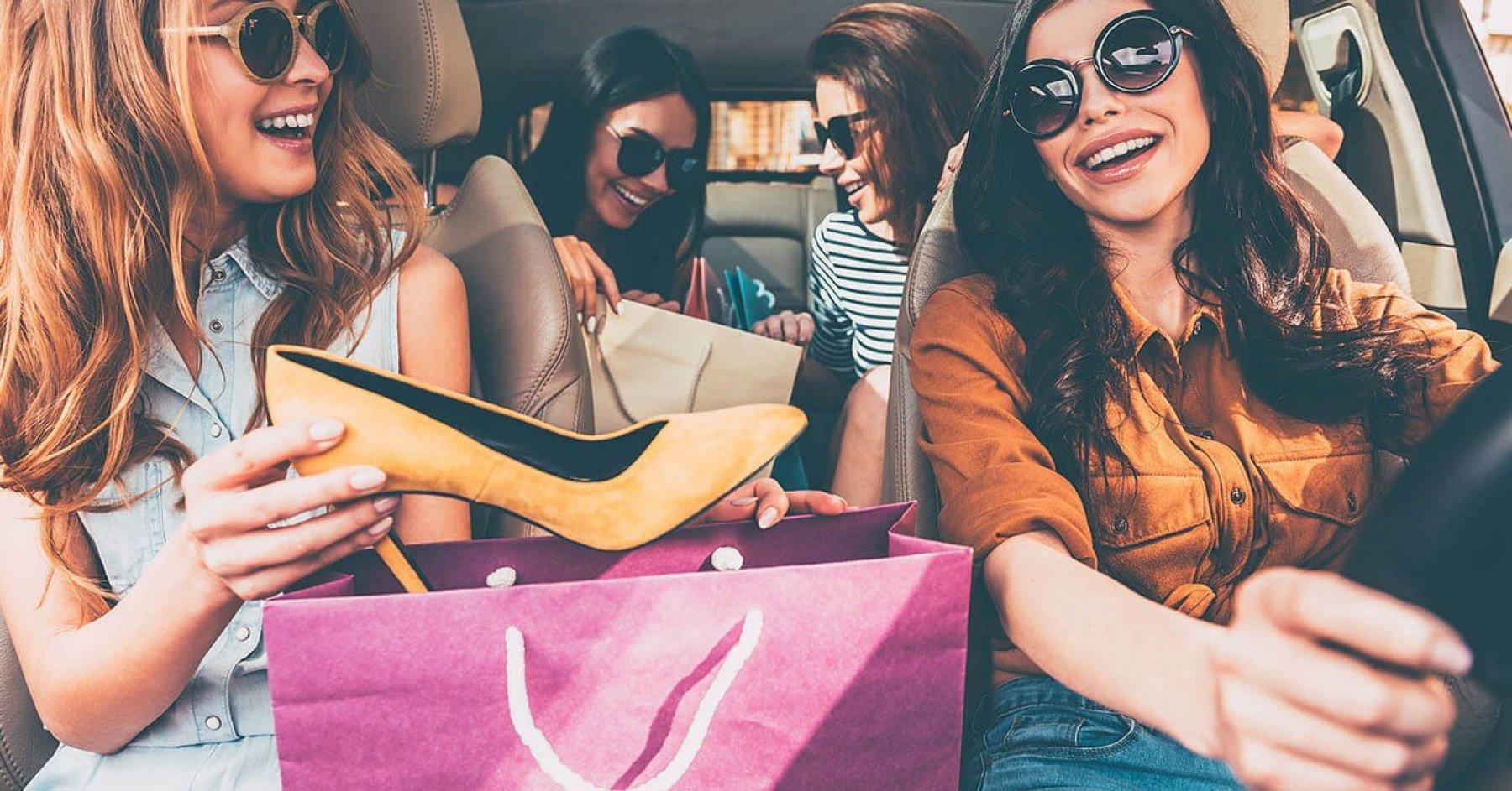 Tjejer i en bil med shoppingkassar