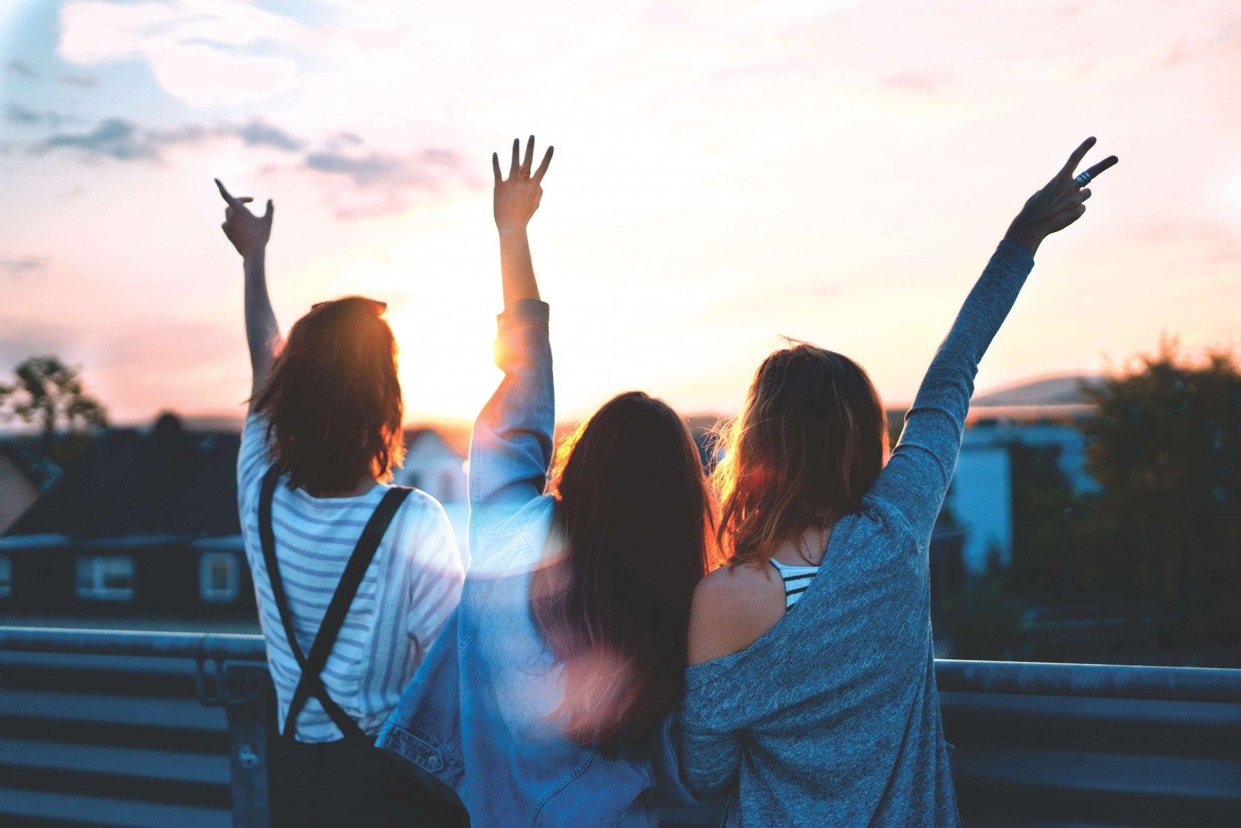 Tre ungdomar står och tittar ut över en solnedgång på en bro