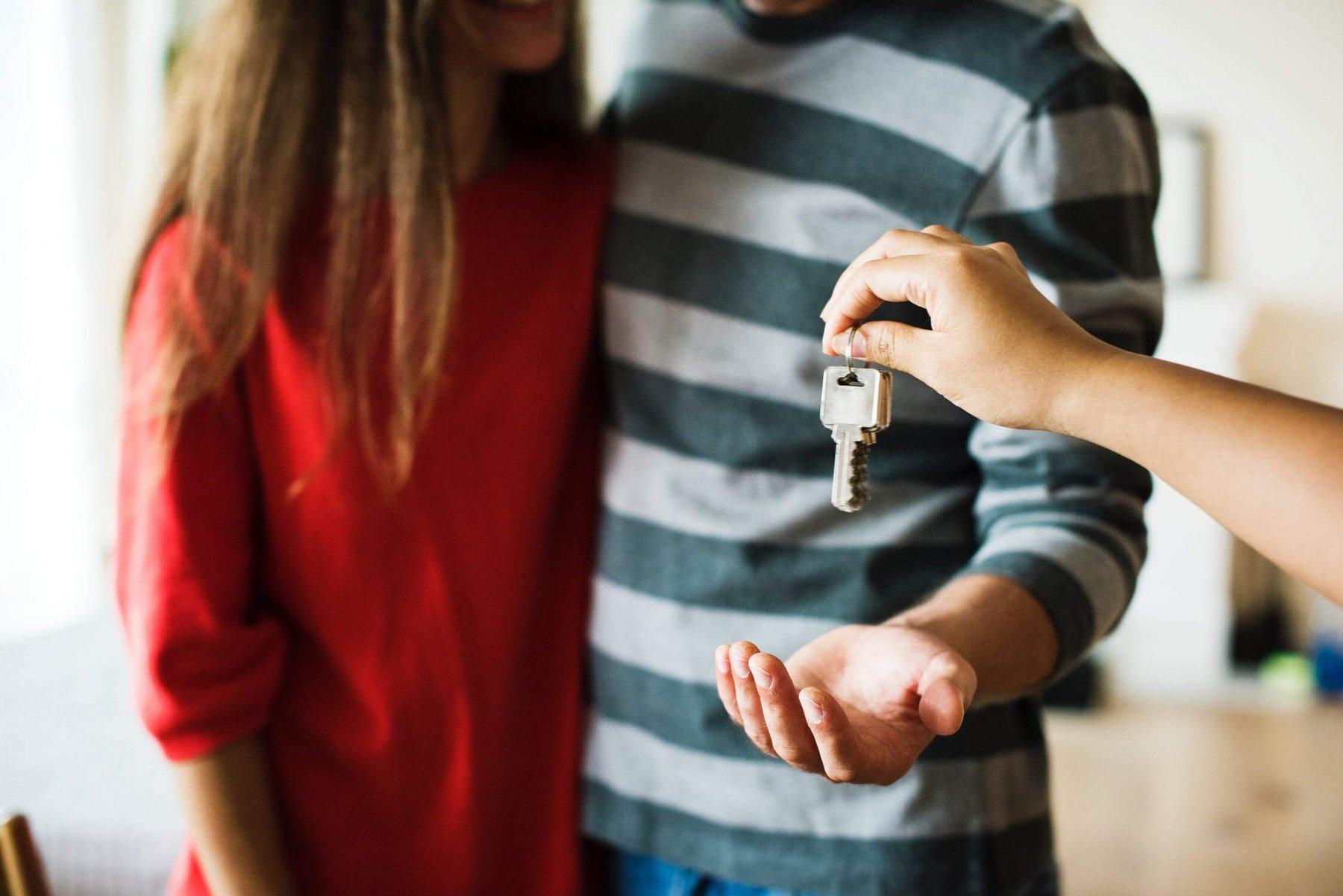 En kvinna i rödtröja och en man i randig tröja tar emot en nyckelknippa