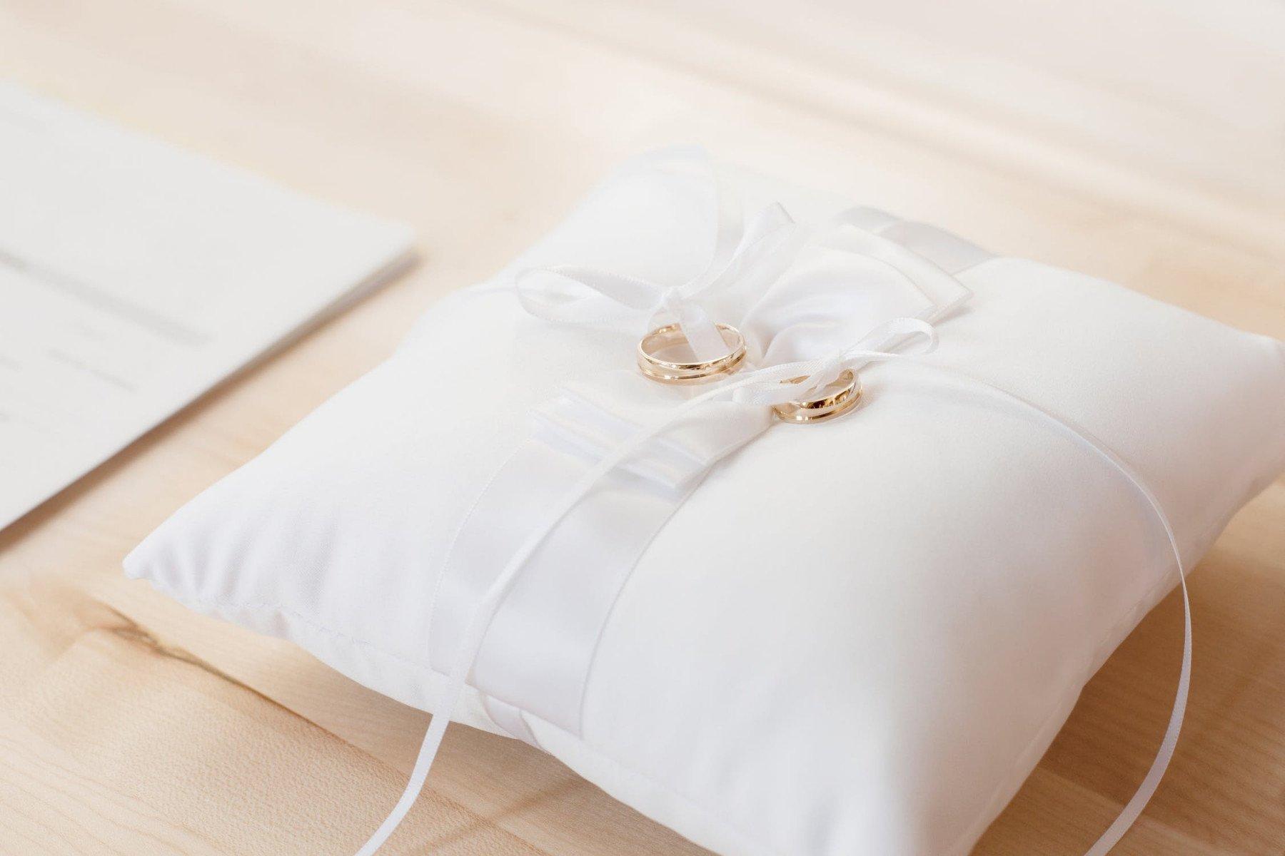 Vit kudde med två vigselringar och knutet vitt band
